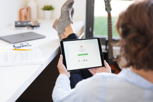 Cisco UCM offers many ways to keep your mobile workforce connected and productive from anywhere | young lady sitting on a chair with feet on desk wearing tan shoes watching an online device with Webex Meetings on screen