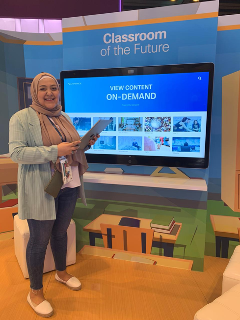 Haya Alzeer stands in front of a Webex Board and a wall that says Classroom of the Future.