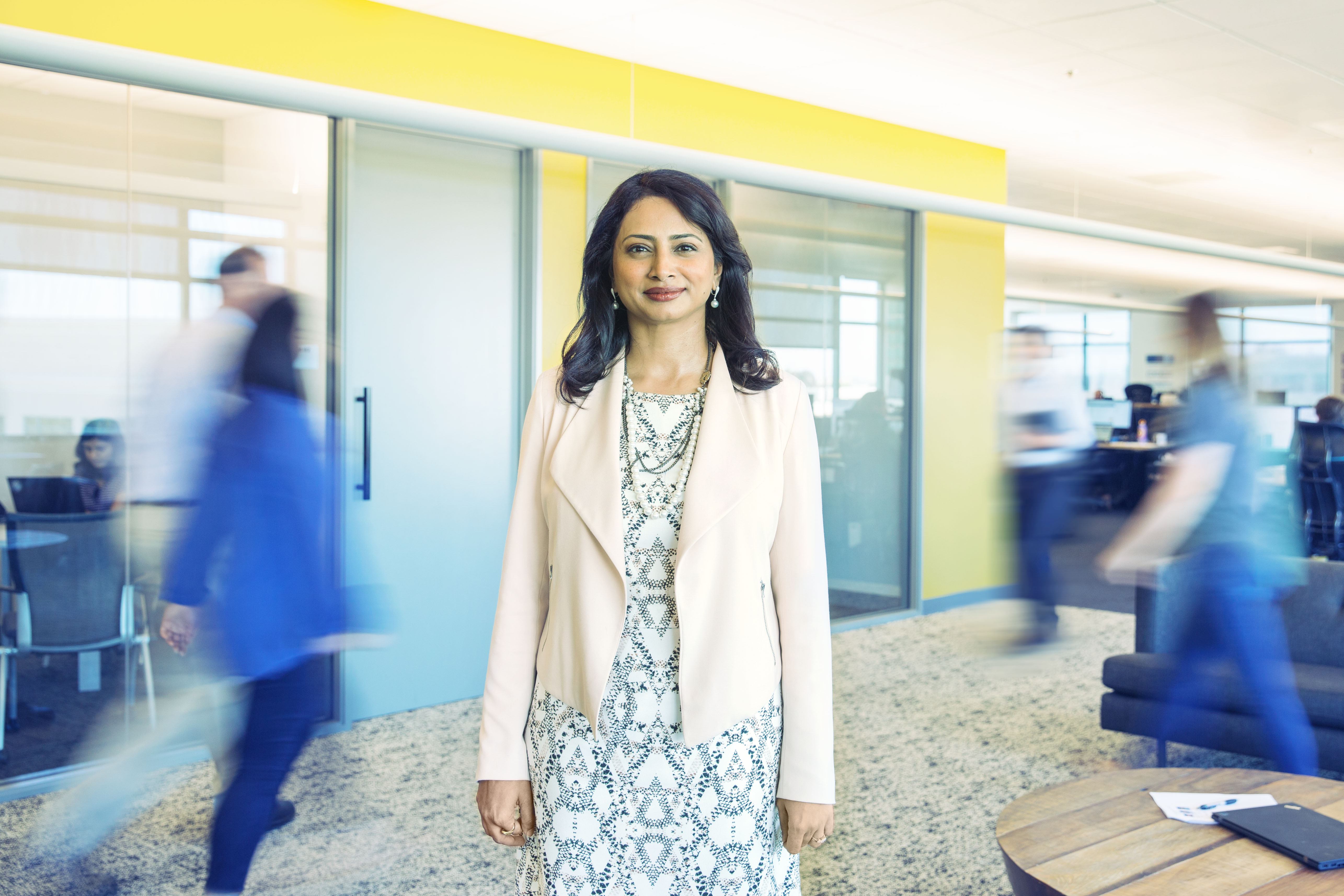 Varsha stands in a Cisco office as people around her are blurred in motion.