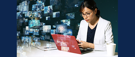 How Webex Keeps Your Collaboration Safe While Working Remotely. Asian Woman working on a red laptop on a white desk, wearing glasses with ai images surrounding her