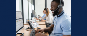 man talking to client wearing headset and working on computer