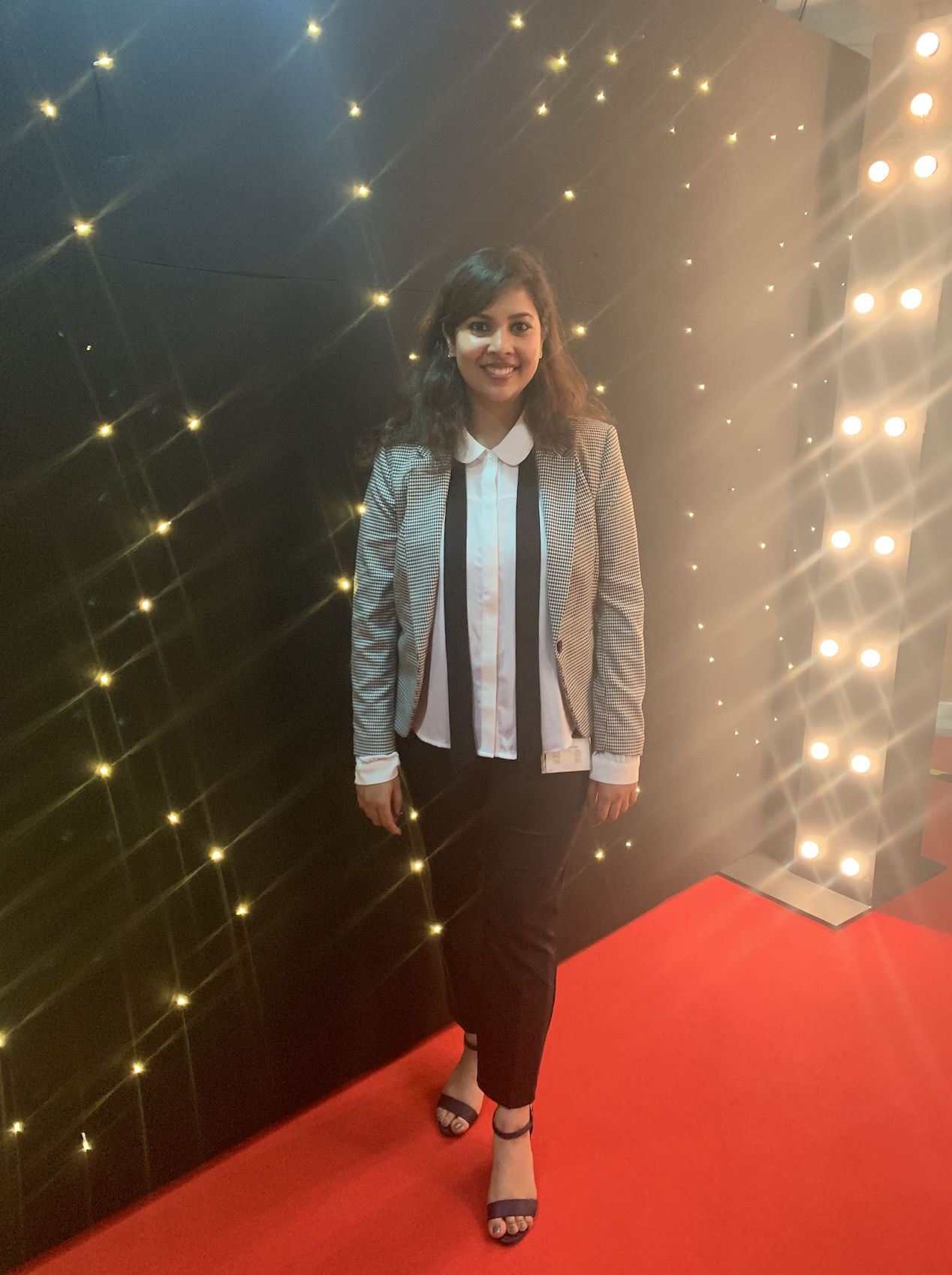 Nikita stands in front of a wall of lights at an event on top of a red carpet.