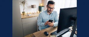 man in blue collard shirt holding and looking at phone while sitting in his office chair in front of his desktop