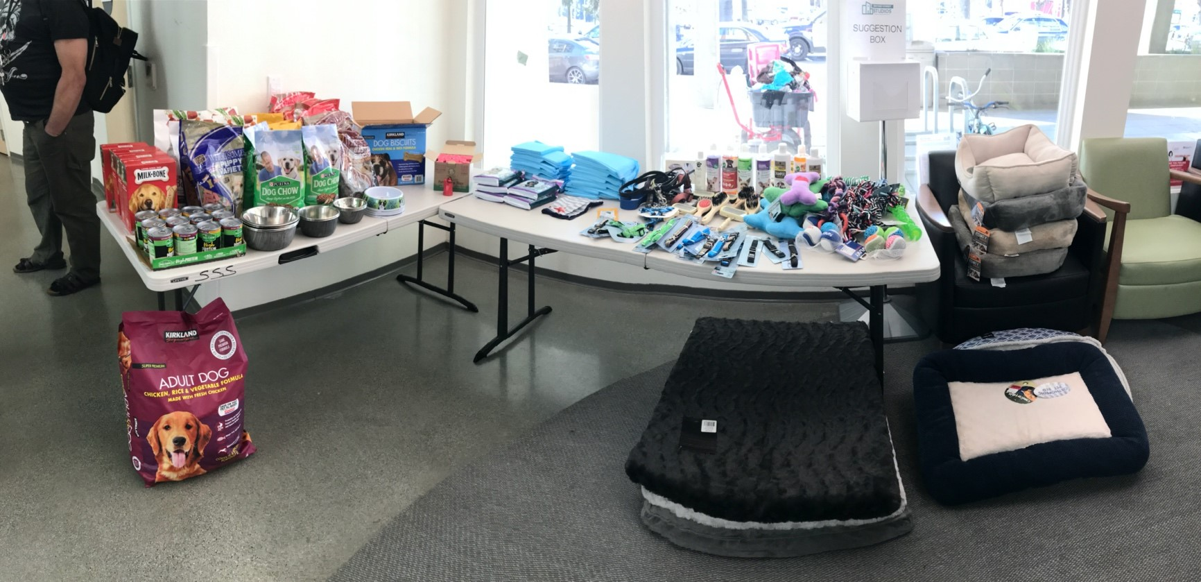 Two tables filled with pet supplies overflowing to the floor and nearby chairs at Second Street Studios in San Jose, California.