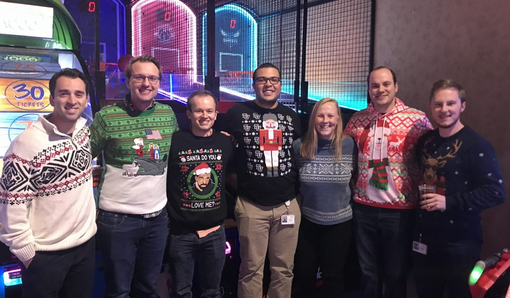 Julian's Cisco team wears holiday sweaters while posing for a group photo.