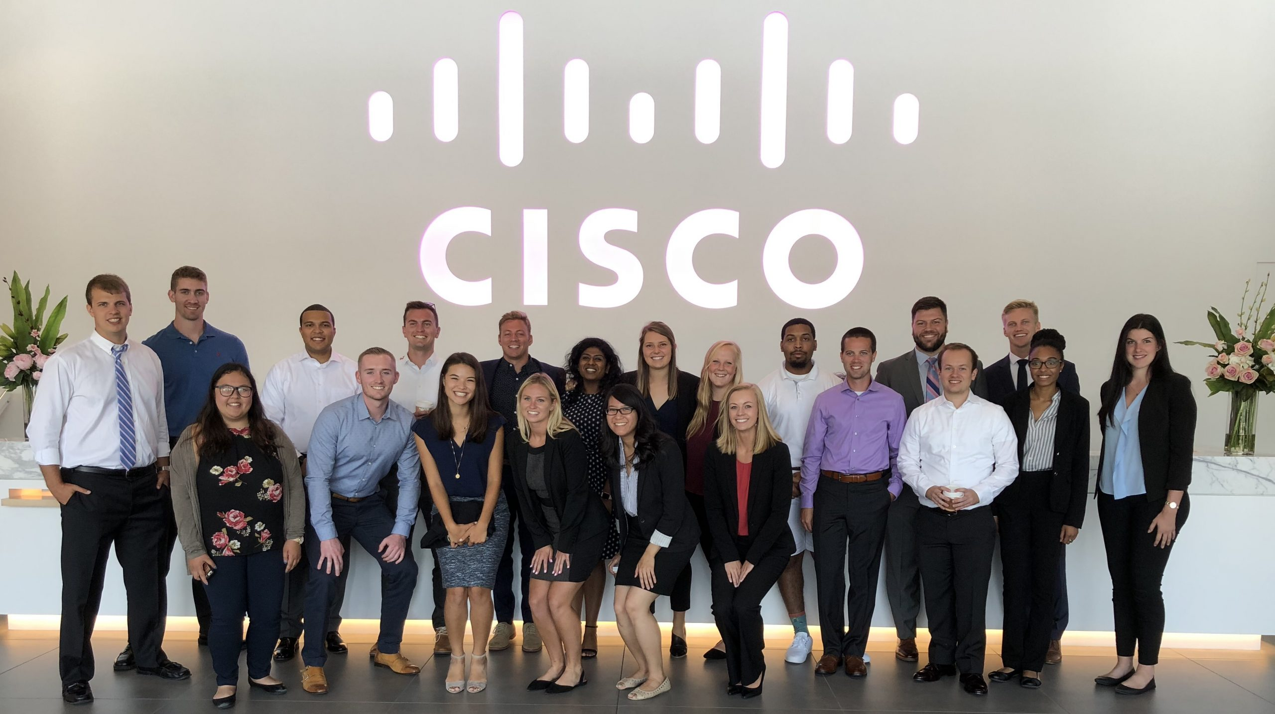 Julain and his teammates stand in a lobby under a giant lit Cisco logo on their first day of onboarding.