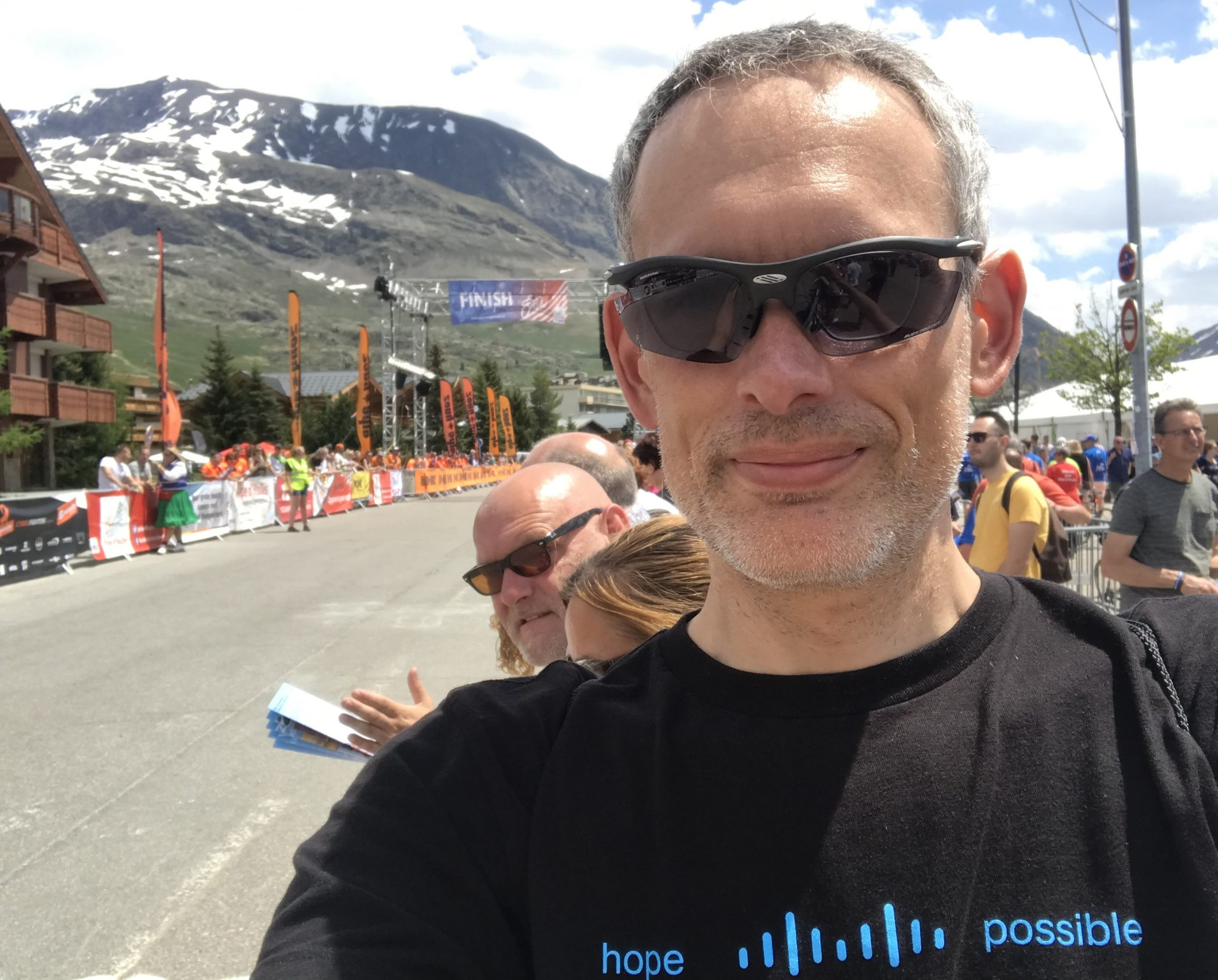 "Mark stands at the finish line wearing a ""Between Hope and Possible there is a Bridge"" shirt."