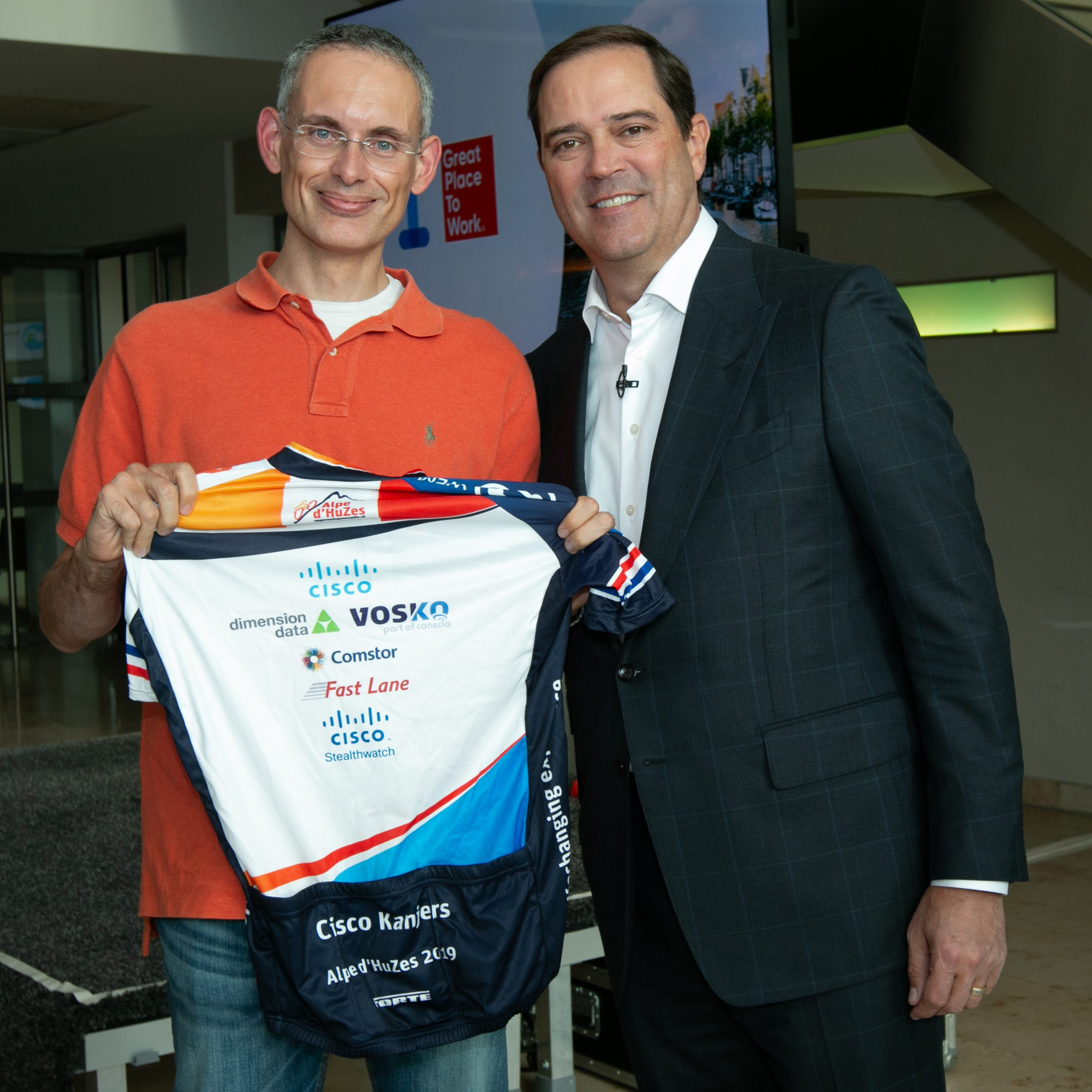 Mark holds his biking shirt smiling next to Cisco CEO Chuck Robbins.