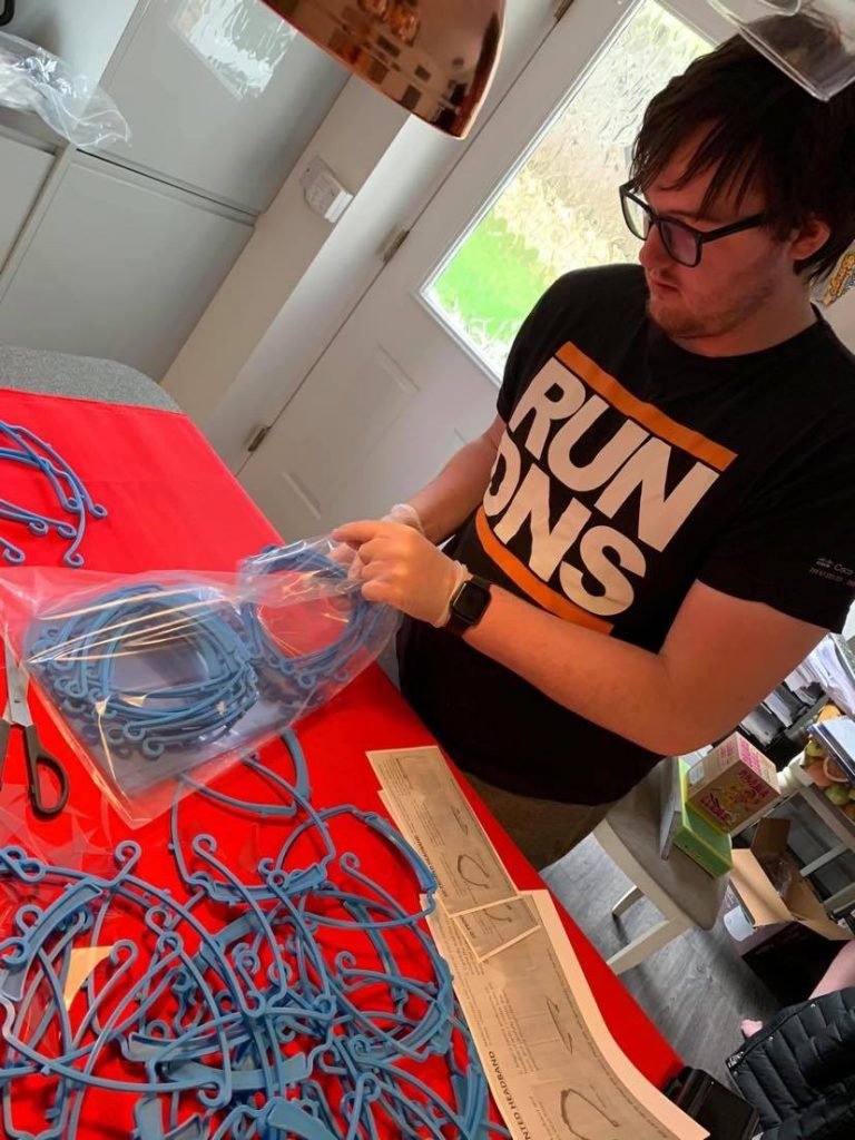 Ollie sets up the work station at home, packing away blue visor fastenors into plastic bags.