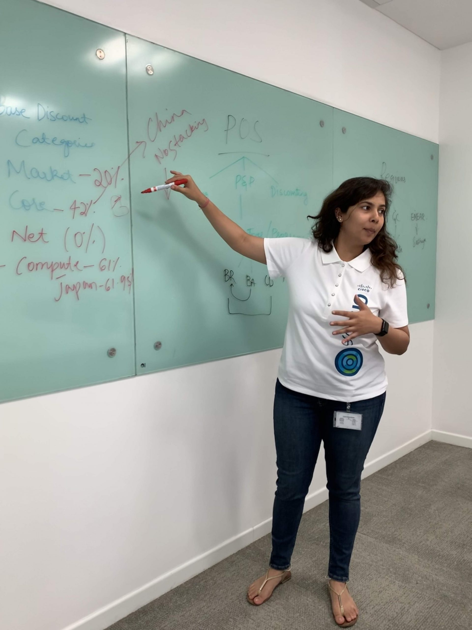 Nikita wears a white Cisco polo and is standing writing on a white board while instructing people watching.