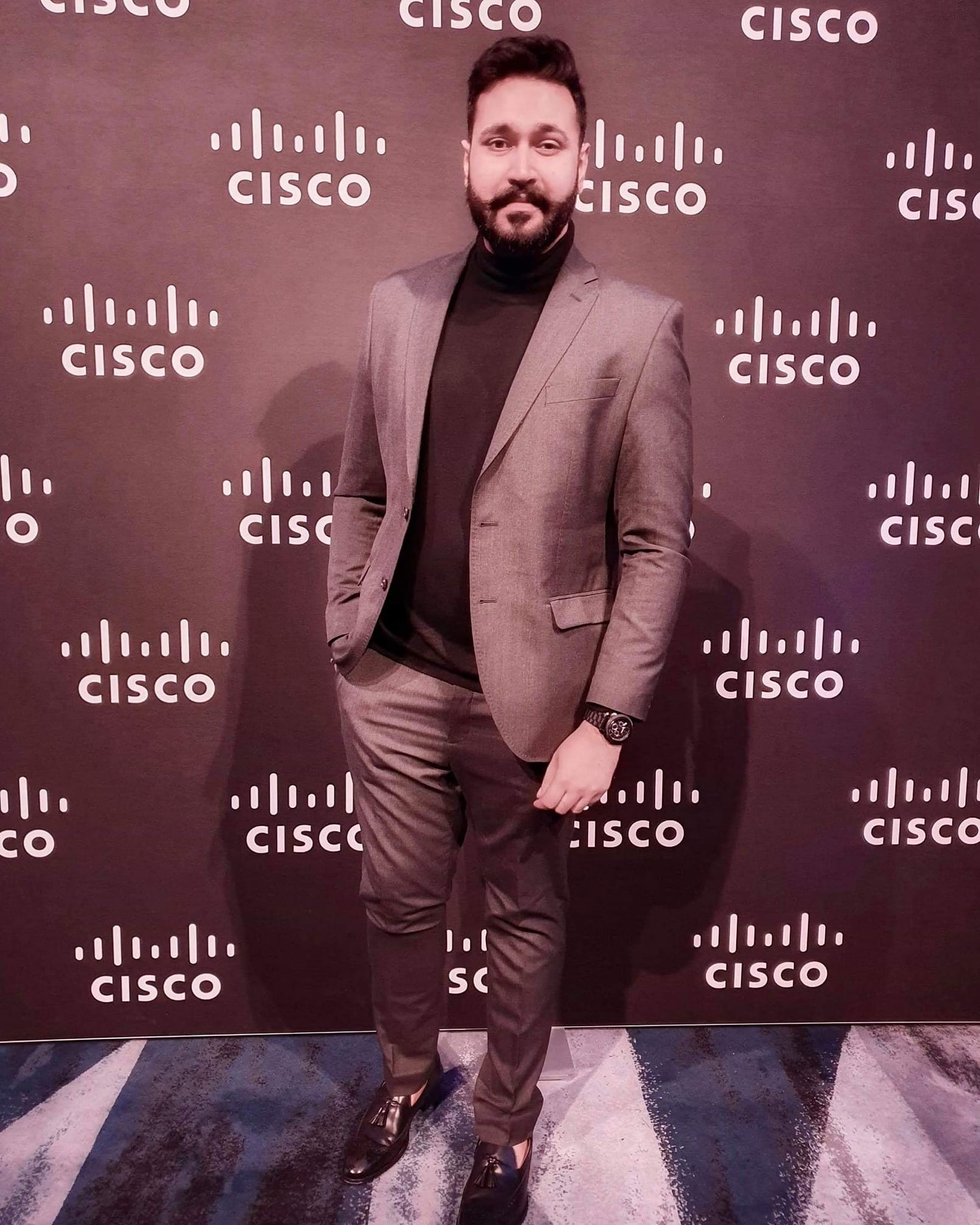 Joy stands in a suit in front of a wall of Cisco logos.