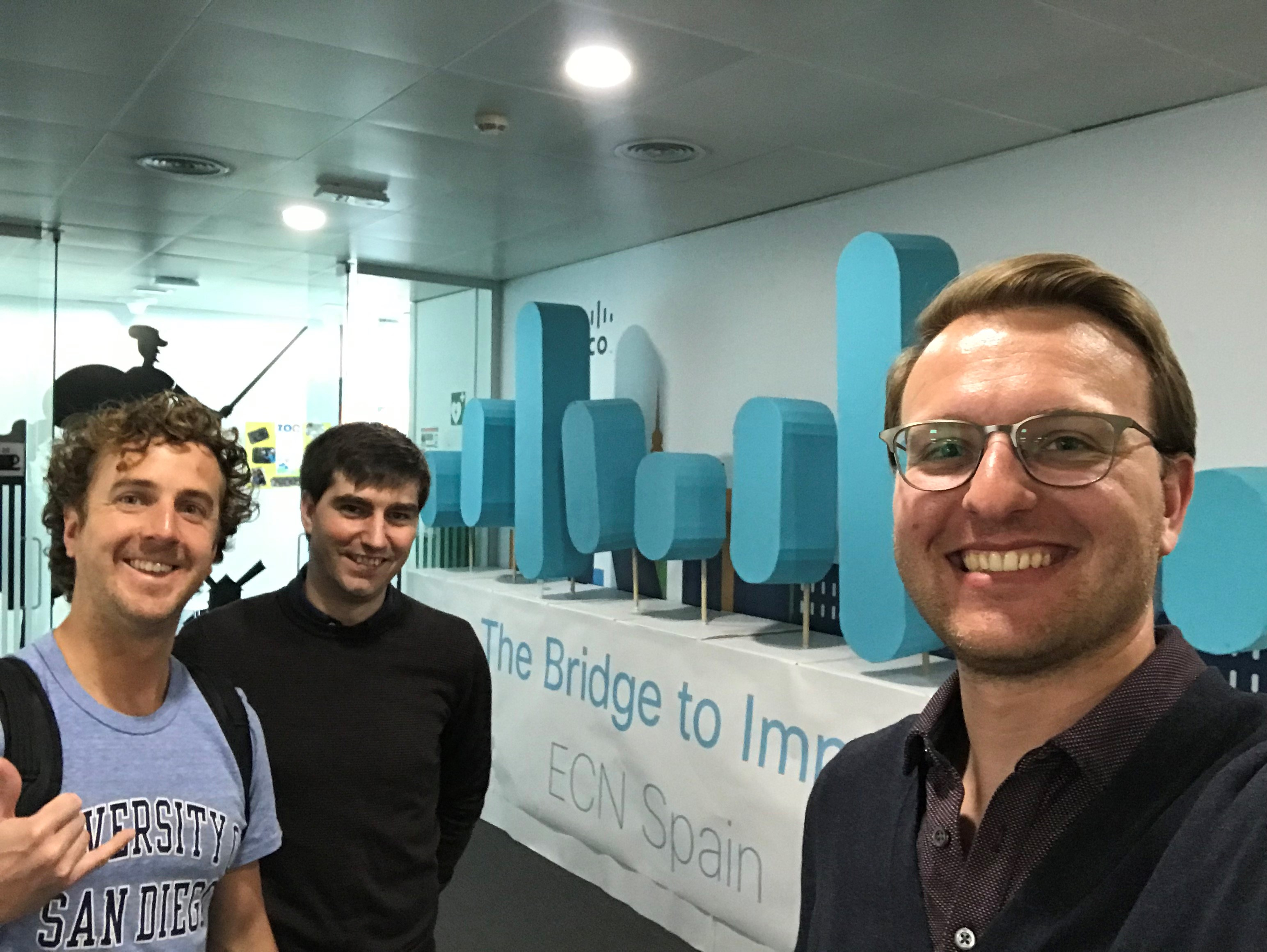 Daivd and his peers stand in front of a sculpture of the Cisco logo at Cisco Spain.
