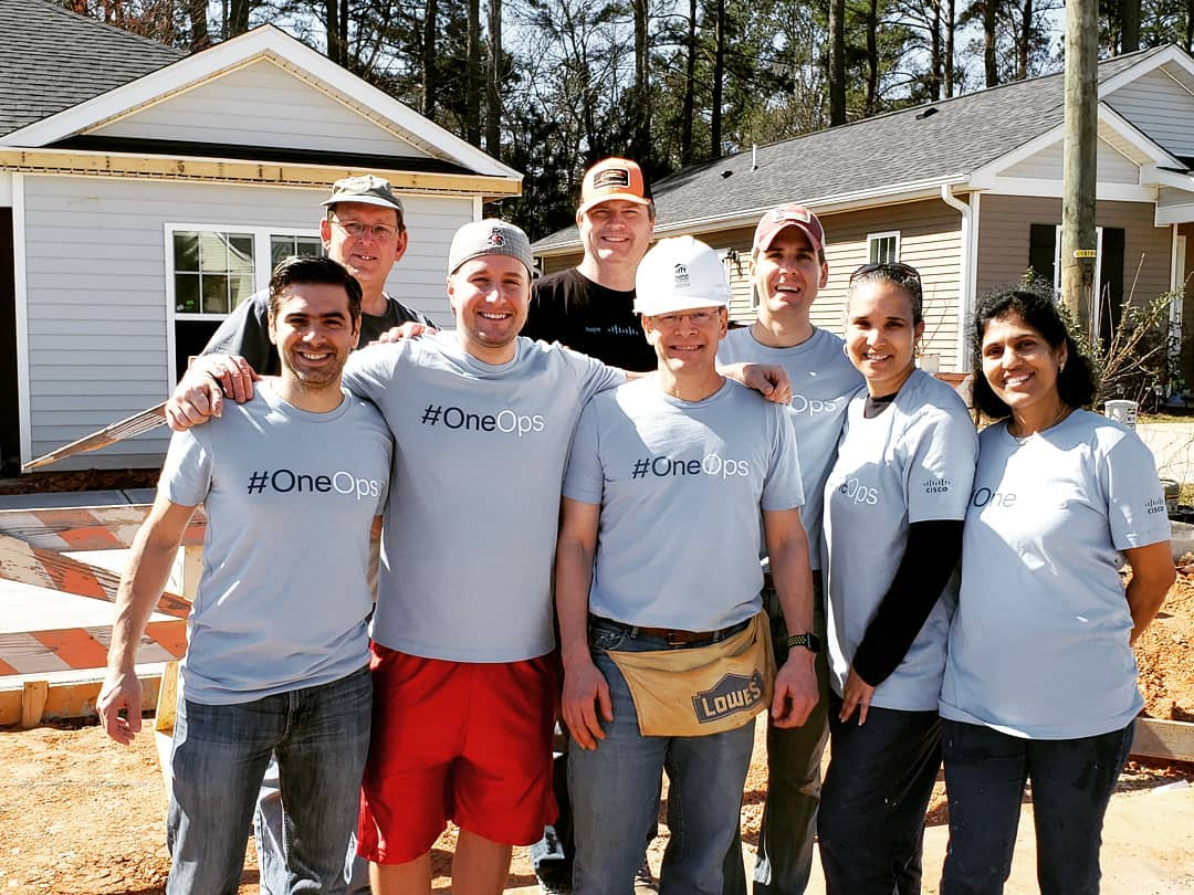 David and the #OneOps team standing together at a give back event building houses.