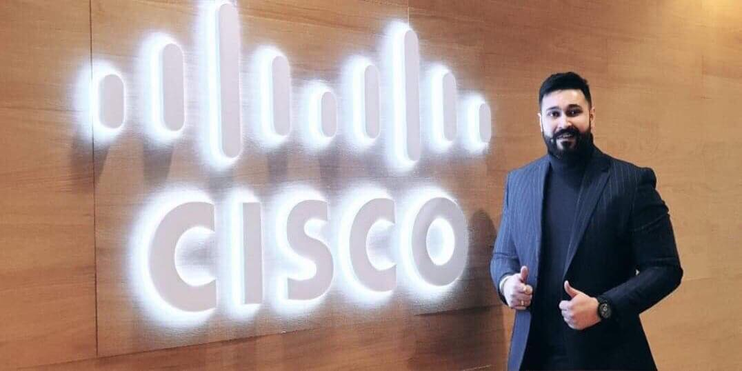 Joy smiles gripping at his blazer next to a light up Cisco sign.