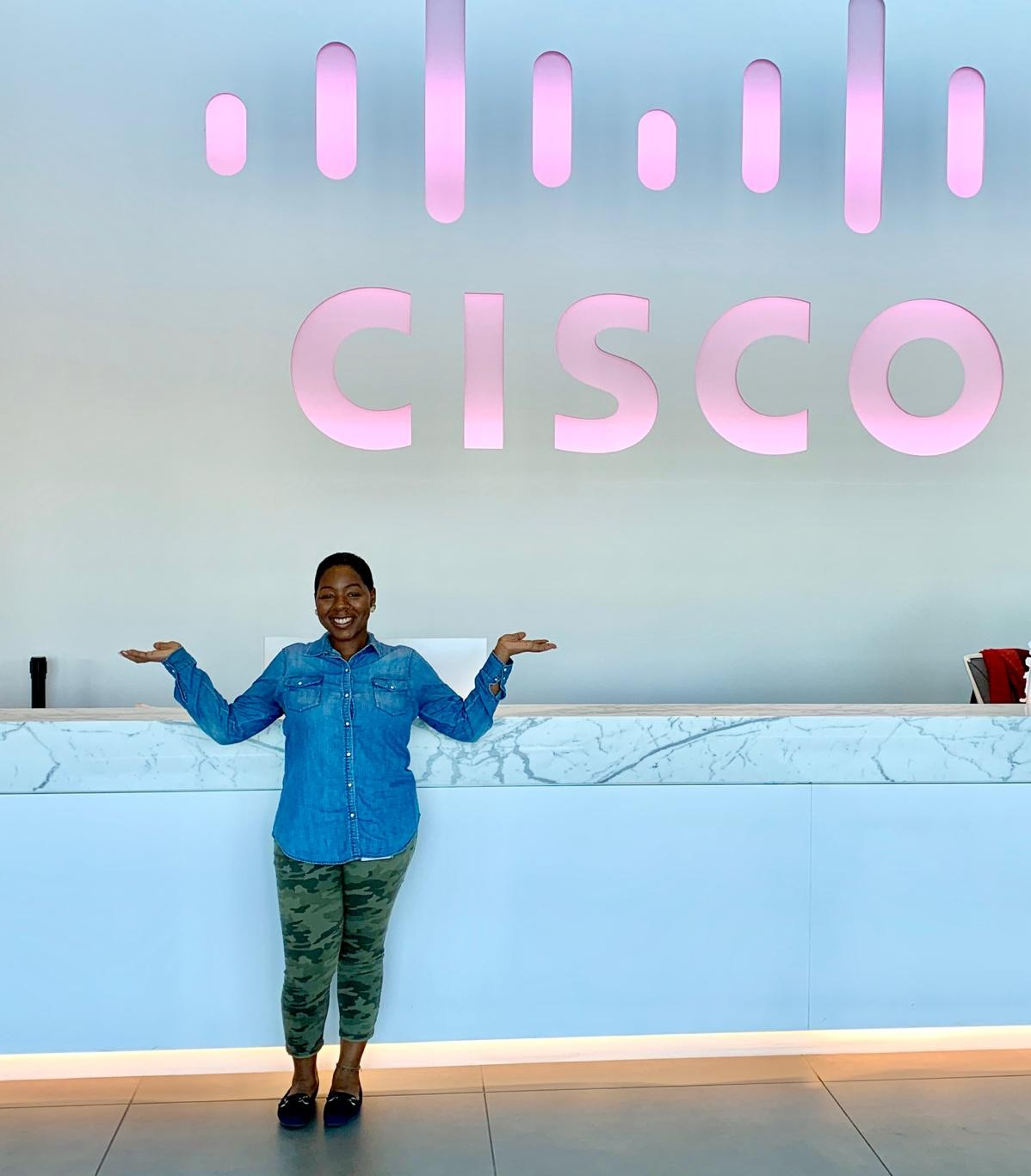 Amber stands in front of a bright pink light up Cisco sign in a lobby of a building.