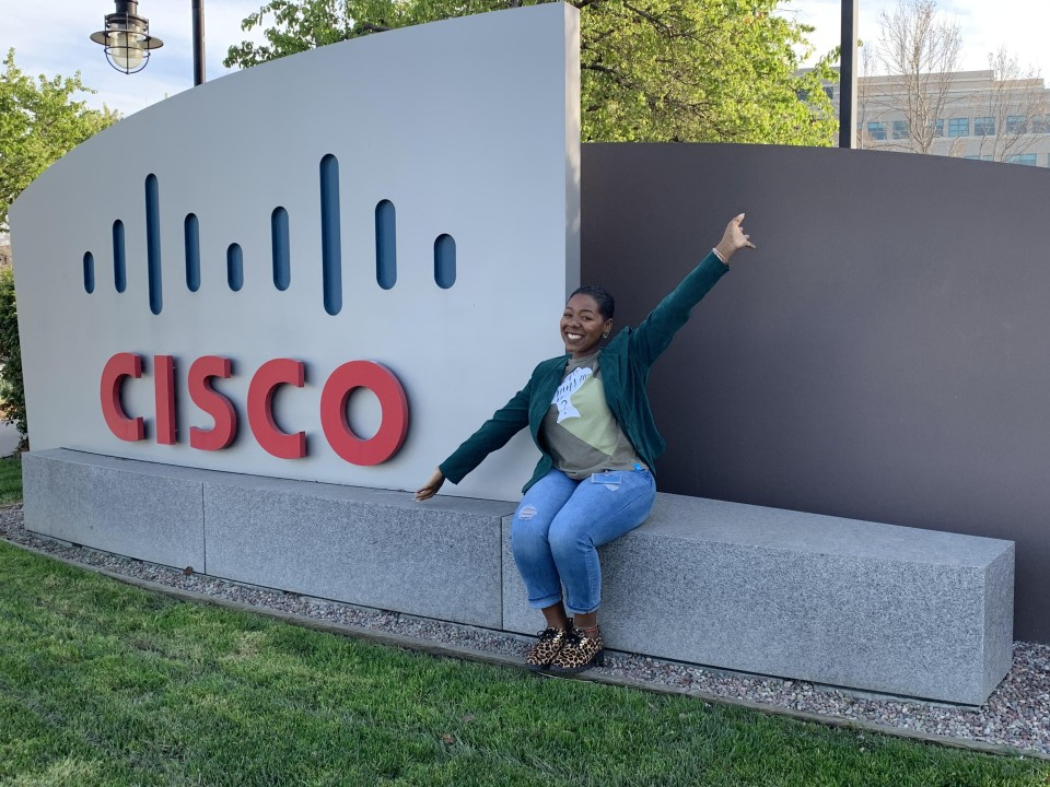Amber smiles with her arms pointed out beside her sitting on a Cisco sign outside of a Cisco campus.