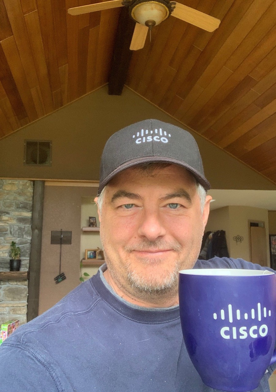 Brett smiles wearing a black hat with a white Cisco logo holding his favorite navy and white Cisco mug.