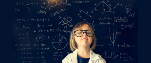 Little girl wearing glasses with Einstein drawings in the background