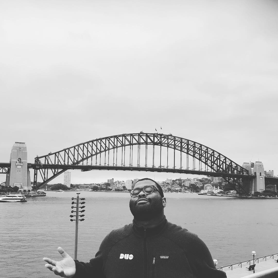 A black and white photo of Karl wearing a DUO branded jacket stands overlooking a bridge in Australia.