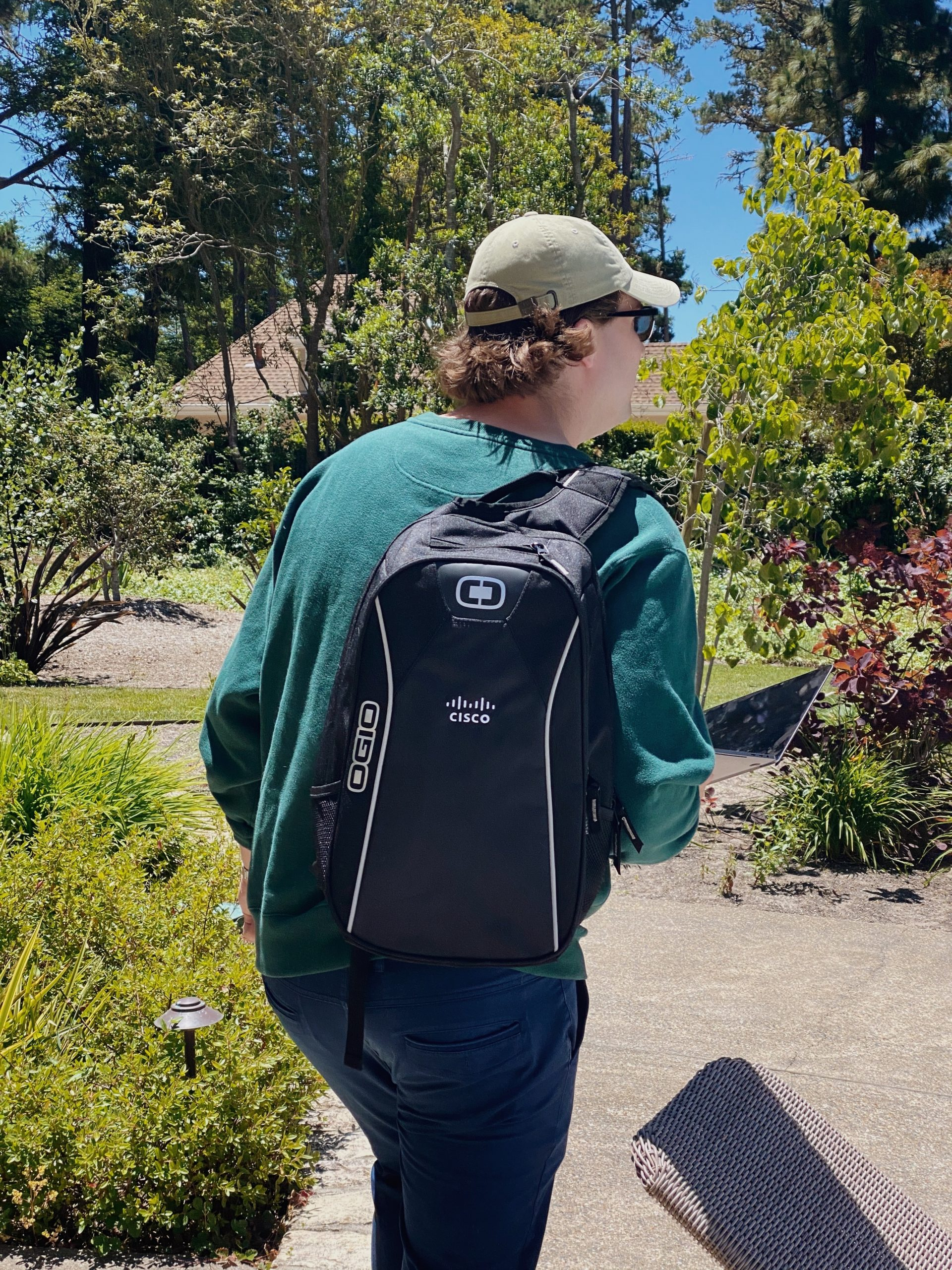 Matthew walks away from the camera with a Cisco branded backpack