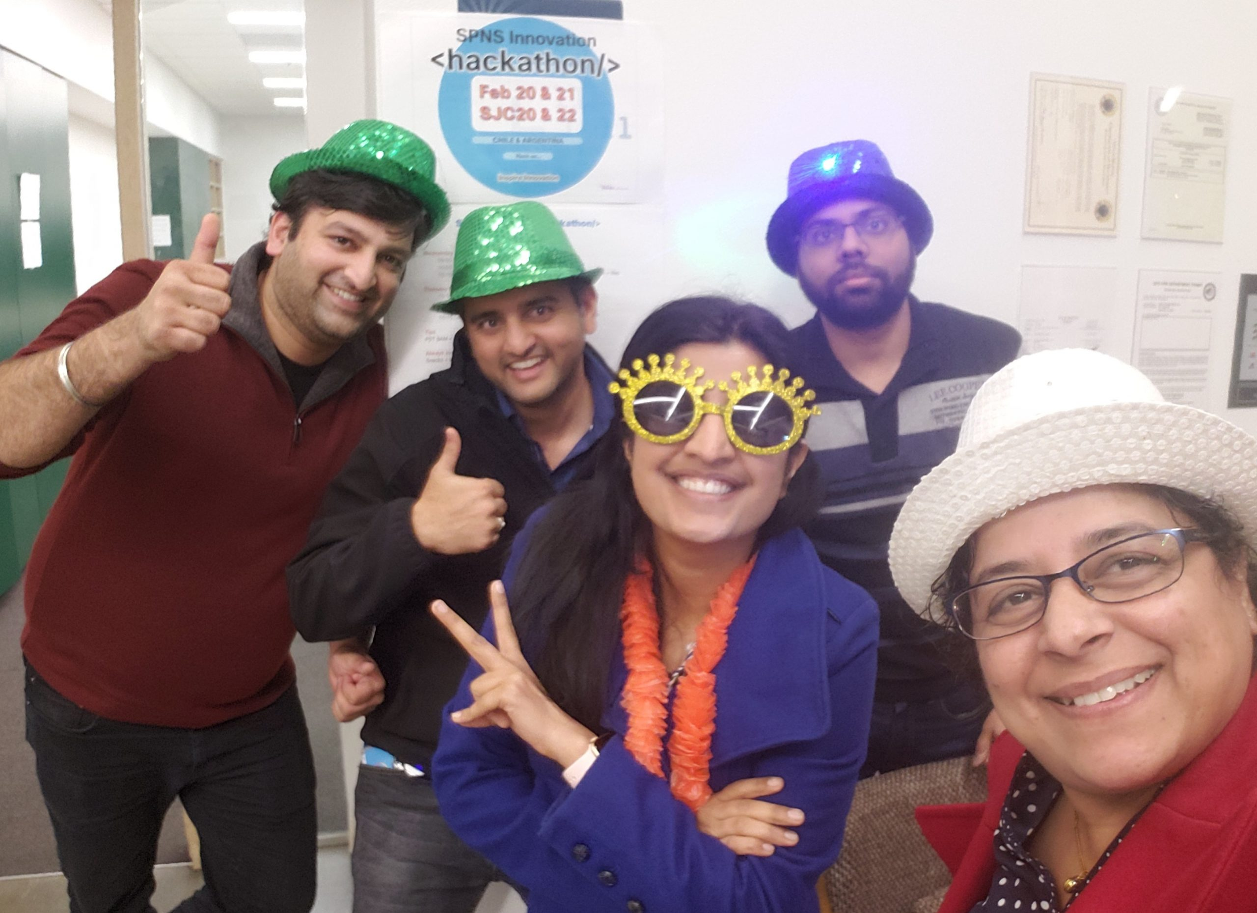 Rashmi and 4 of her peers wear silly hats and glasses under a SPNS Innocation Hackathon poster.