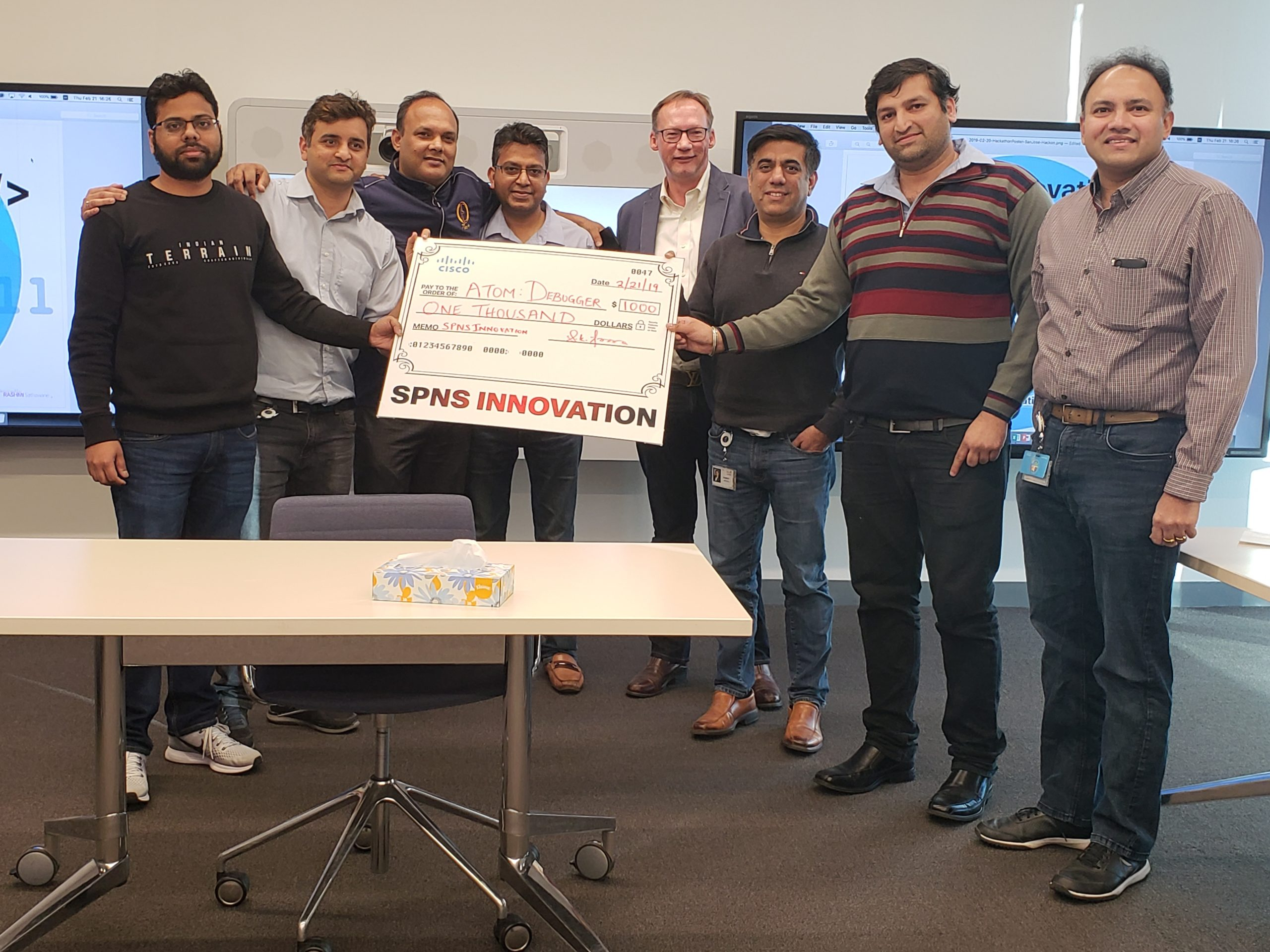 A group of Rashmi's friends and colleagues holding a large check with the words SPNS INNOVATION across the bottom.