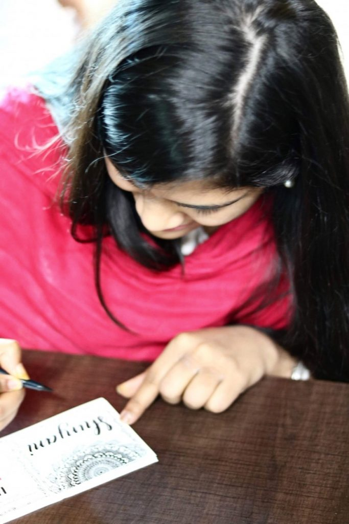 Diparati signs Women's Day cards at Cisco with her artwork.