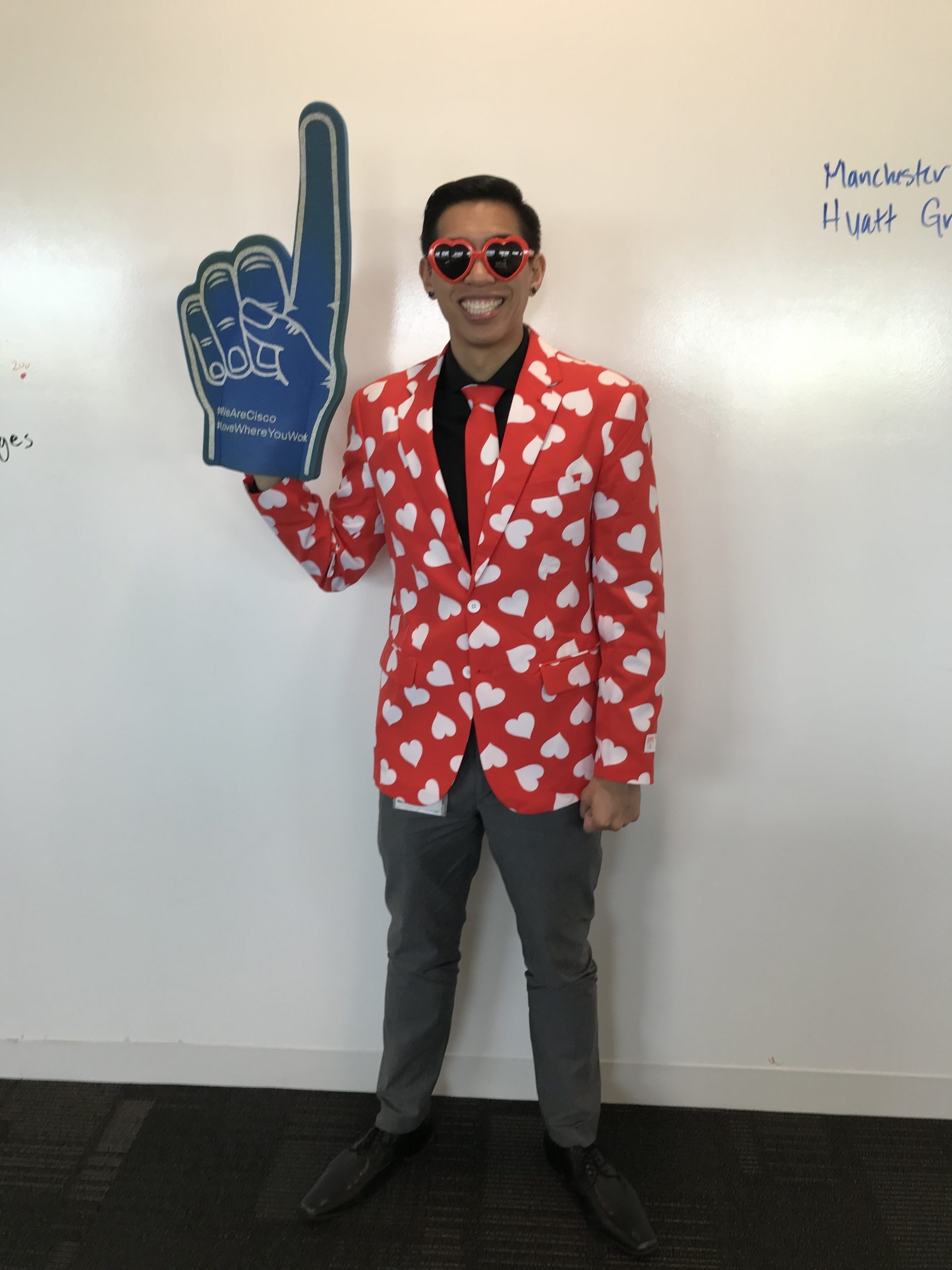 "Justin wears a heart suit and a ""#1 foam finger"" to celebrate Cisco's #1 World's Best Workplace."