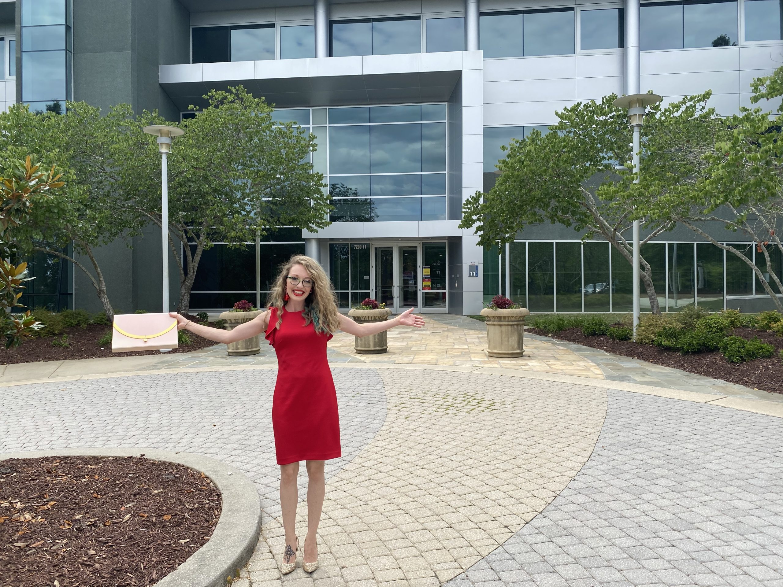 Miranda holds out her arms and shares a big smile in front of a Cisco building in RTP.