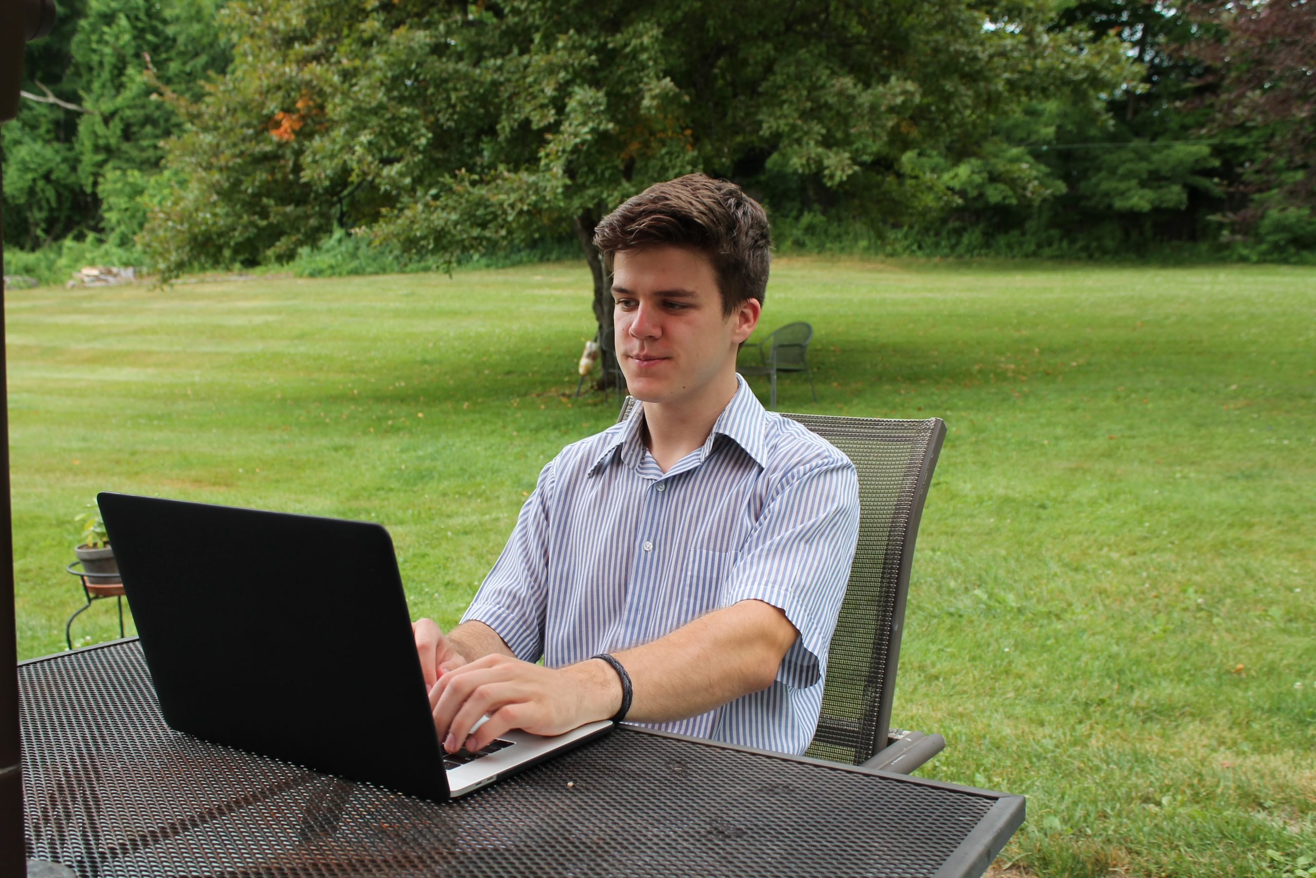 Carl sits outside while working on his laptop.