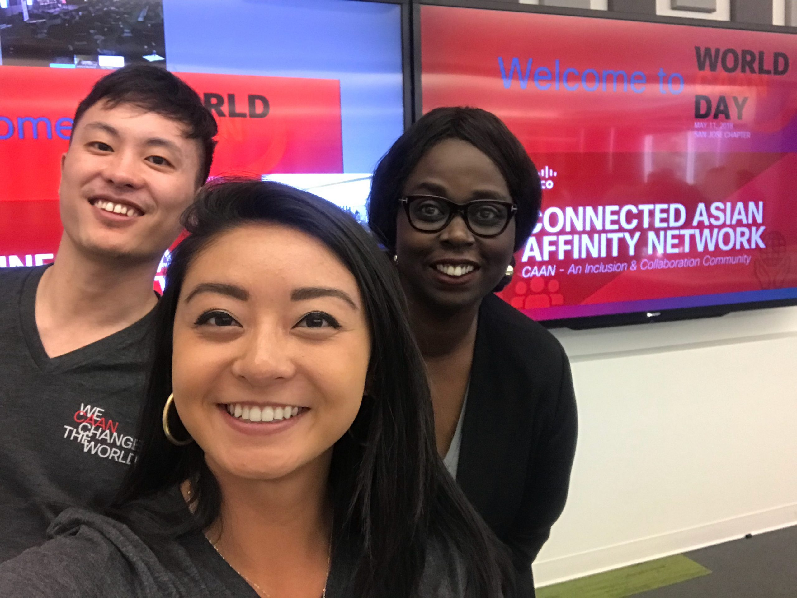 Melissa smiles with two of her peers in front of two tv's with the Connected Asian Affinity Network logo displayed.