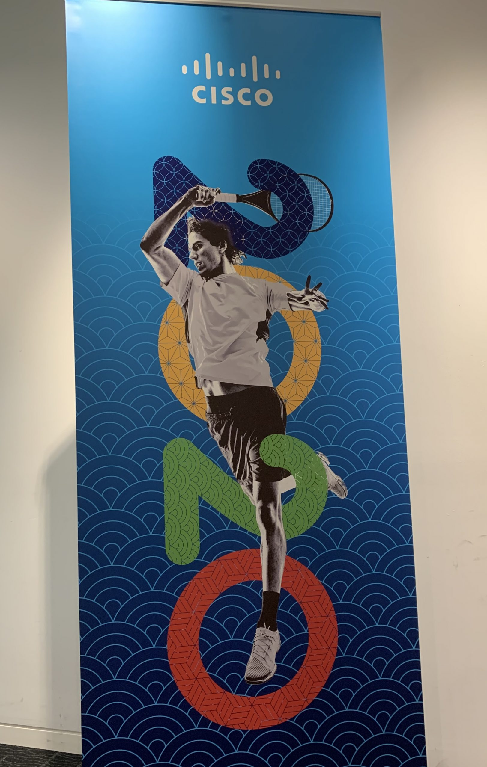 A Cisco banner with a person swinging a tennis racket intertwined with 2020