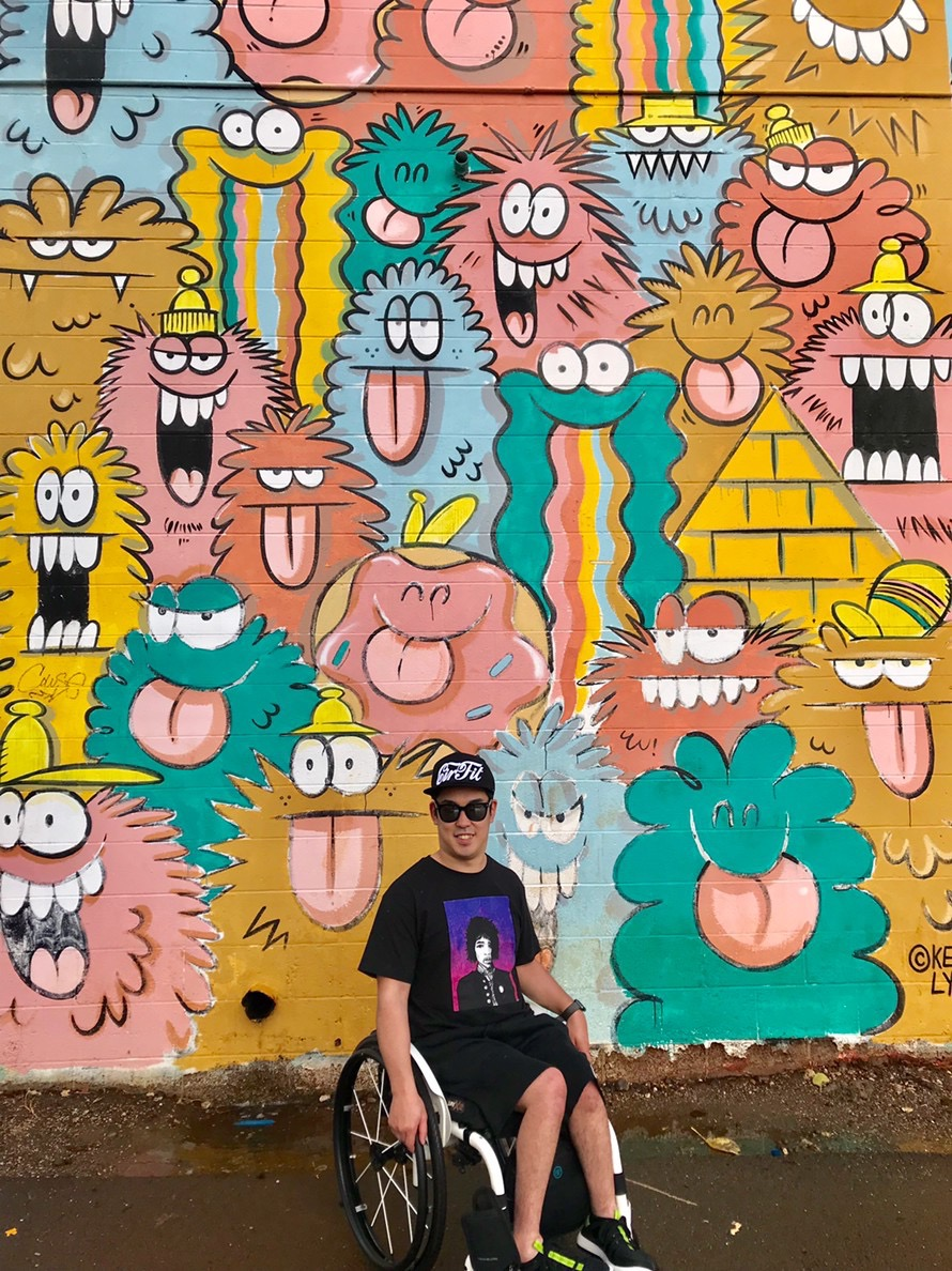 Hideaki wears a hat and sunglasses in front of a colorful mural.