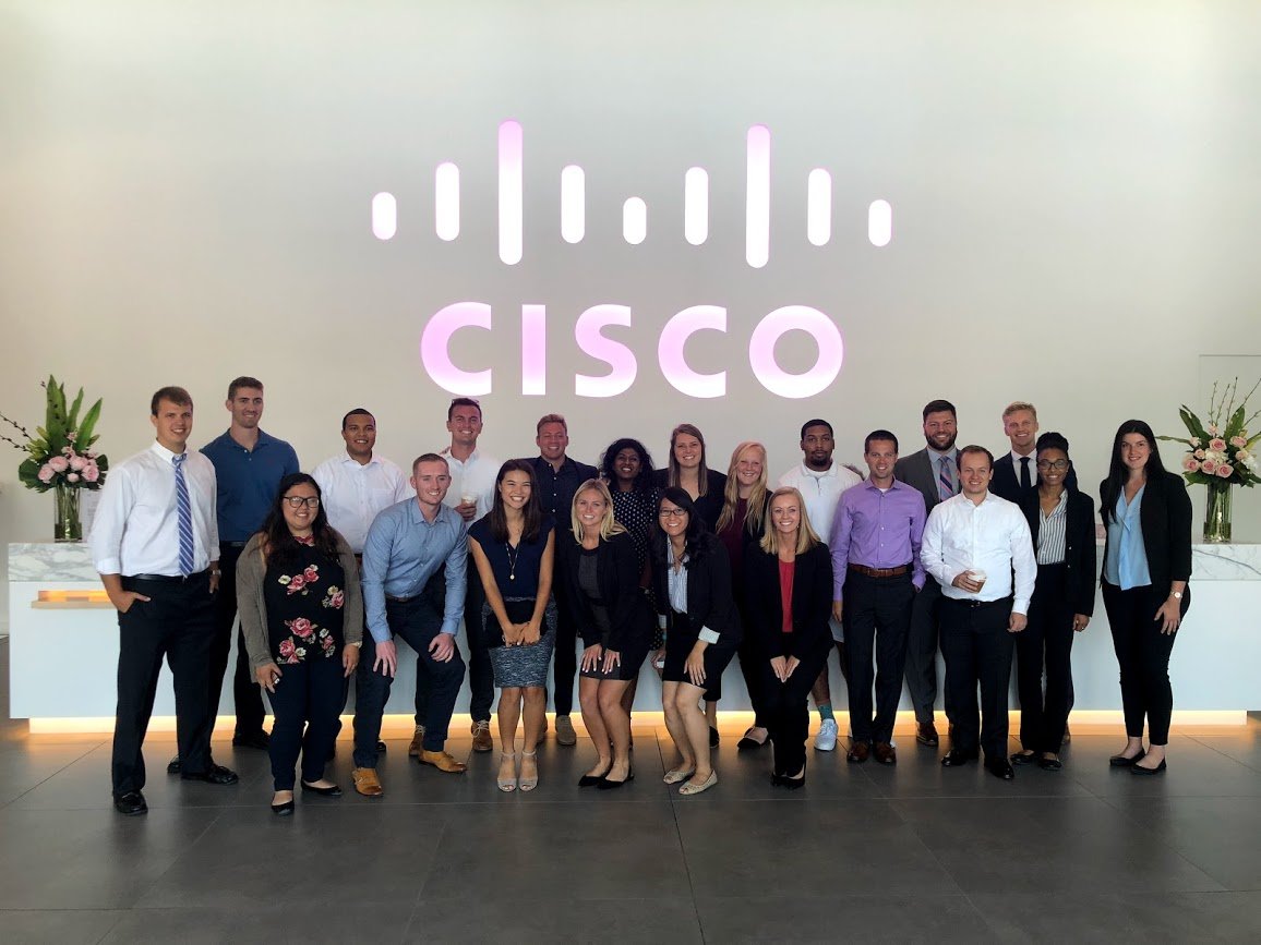 Prabha's Cisco LIFT Class in a Cisco lobby with a pink light up Cisco sign behind them.