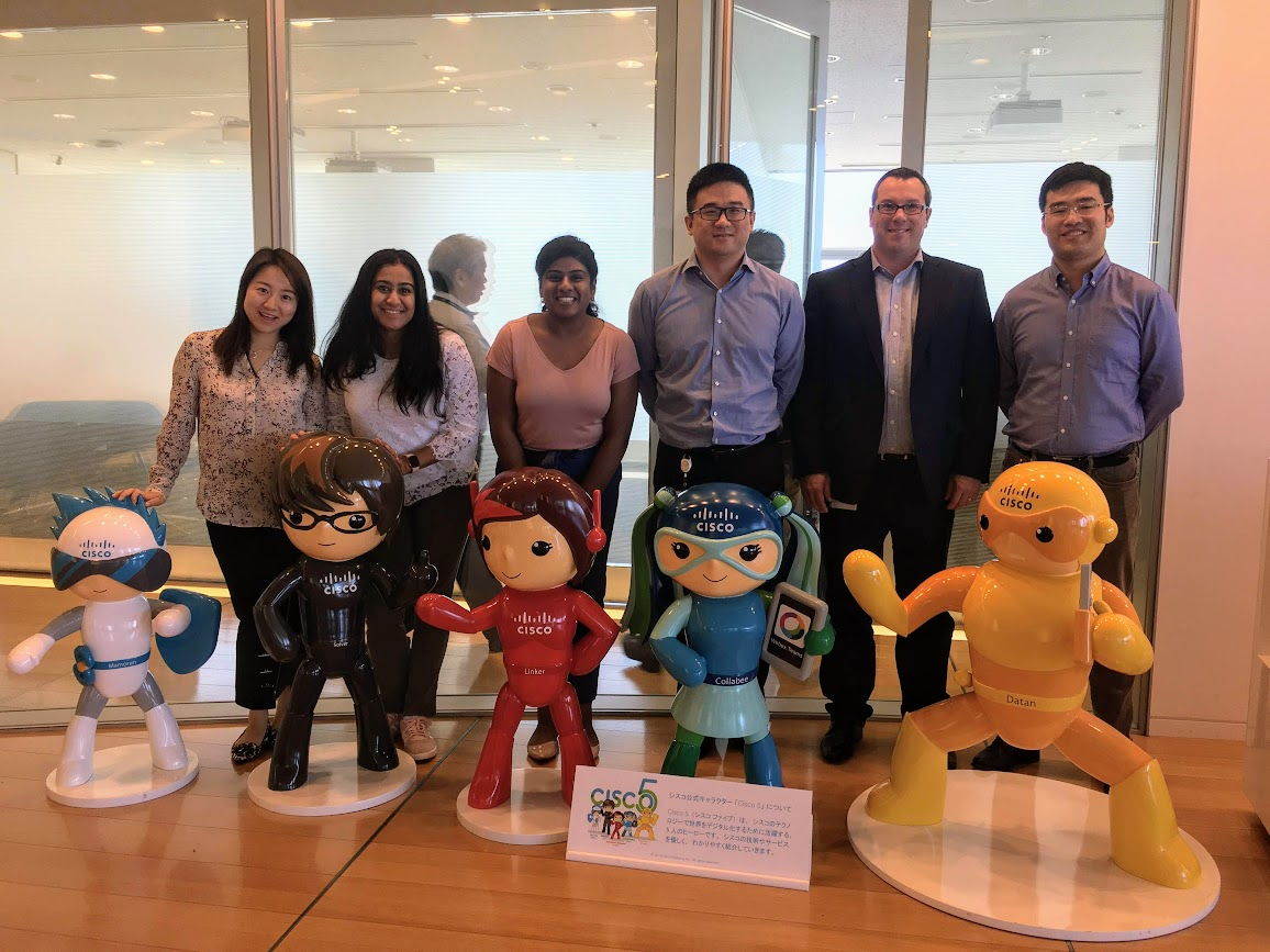 """Prabha and her team stand with the """"Cisco 5"""" in the Japan office."""
