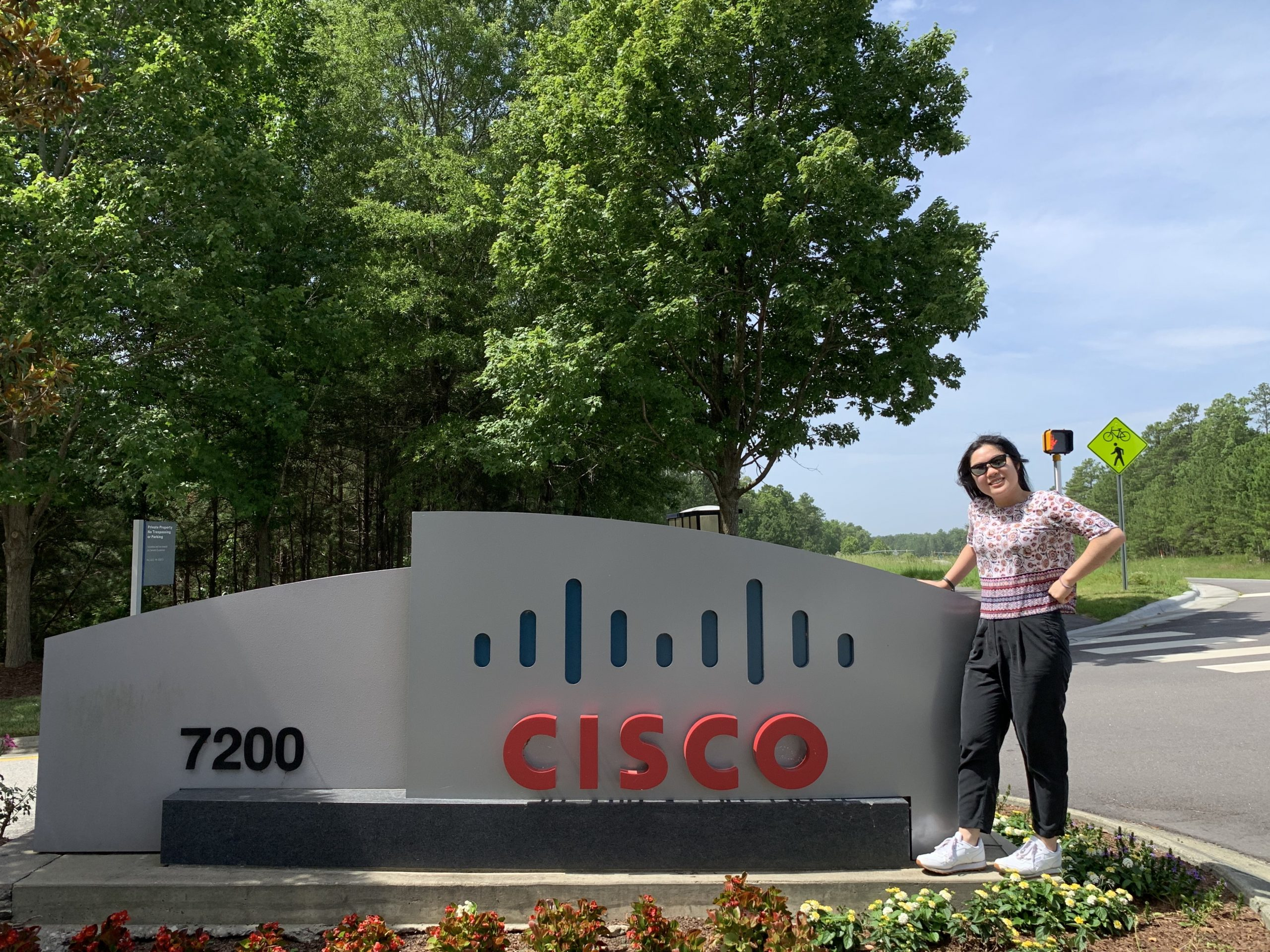 Rashona stands proudly next to a Cisco sign outside at our RTP campus.