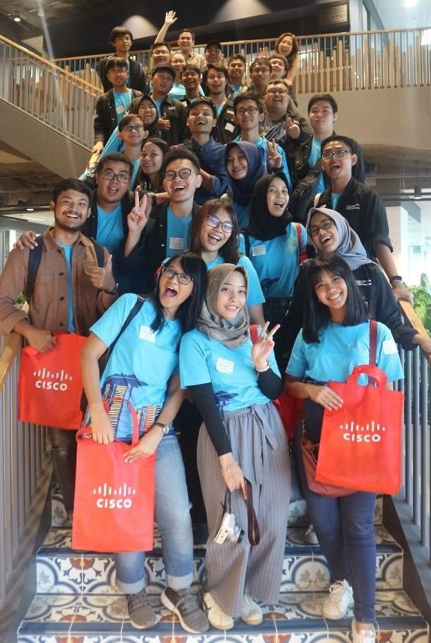 Students from the University in Indonesia smile on a staircase holding Cisco bags.