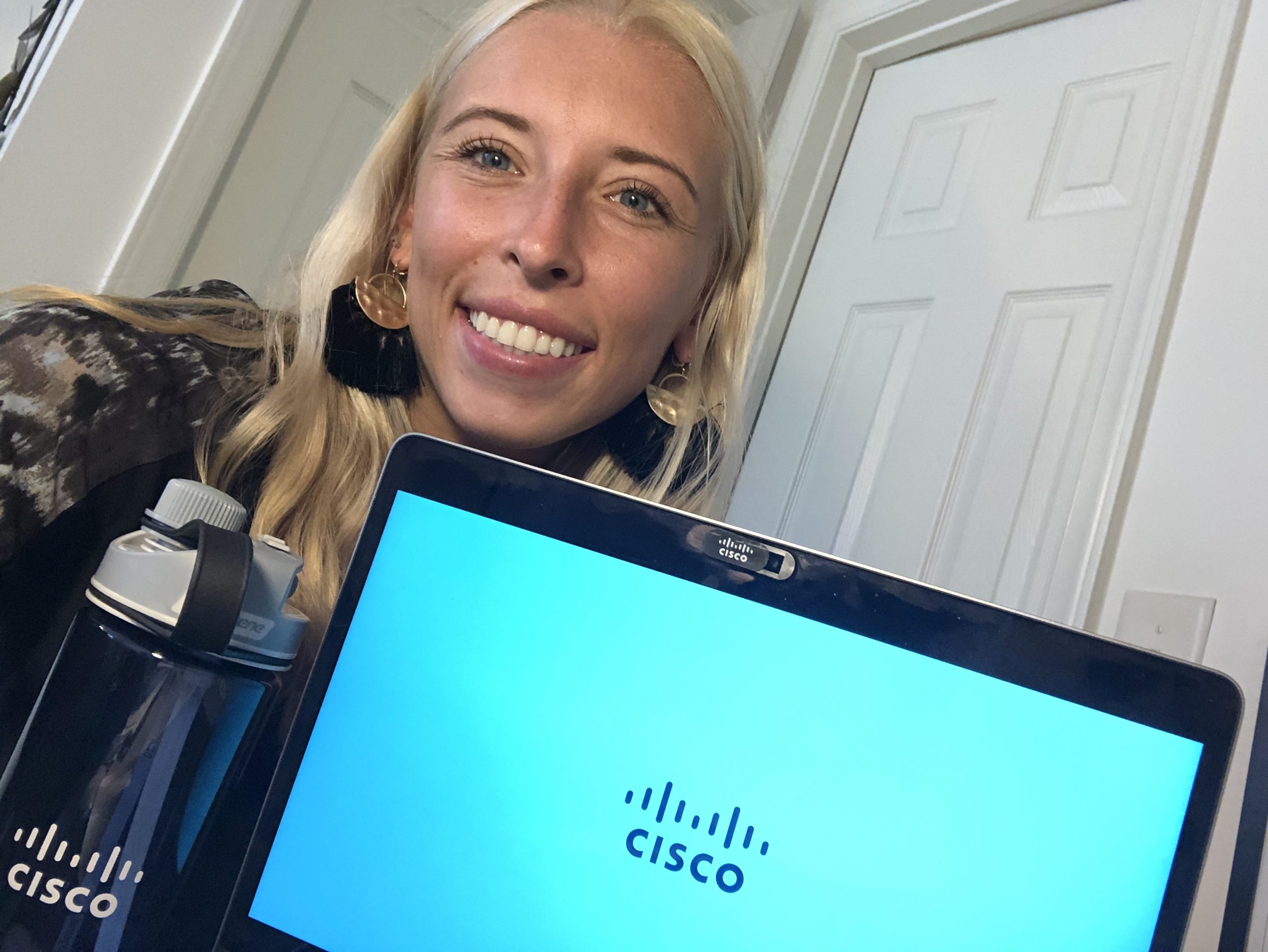 Courtney smiles behind her Cisco laptop and branded water bottle.