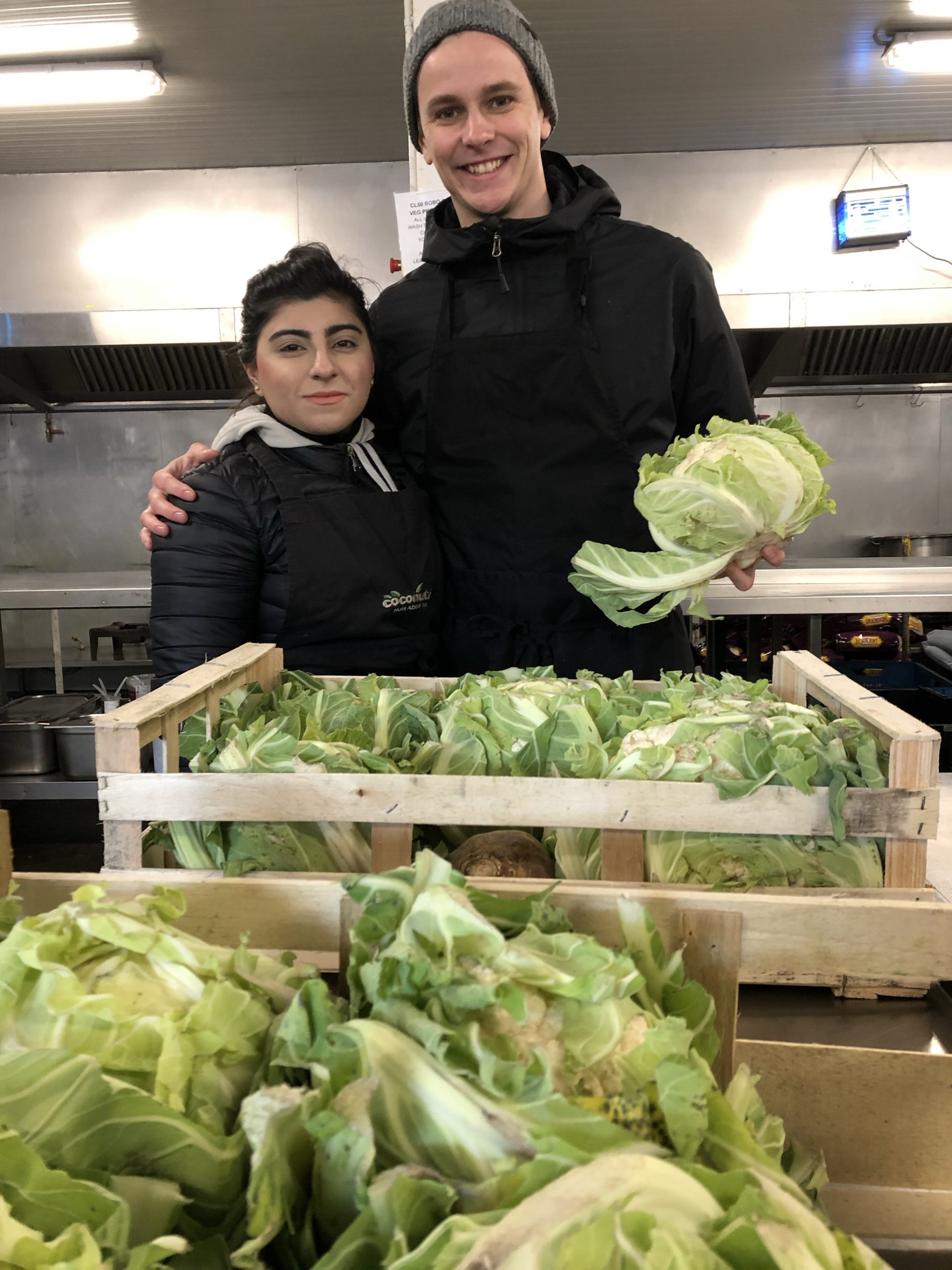 Nico stands with his peer behind boxes of lettuce in The Jungle's kitchen area holding a head of lettuce.