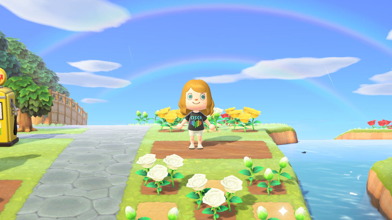 Carmen stands under a double rainbow in her Cisco Pride tshirt on her Animal Crossing island.