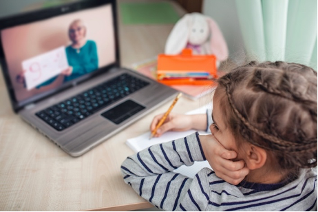 child sitting at a computer doing distance learning