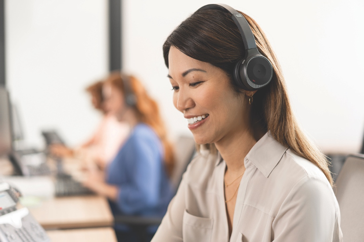 Female customer service agent wearing Cisco Headset 730 with bluetooth sitting at her chair smiling