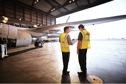 Two men on a hangar talking to each other wearing yellow jackets standing in front of an airplane