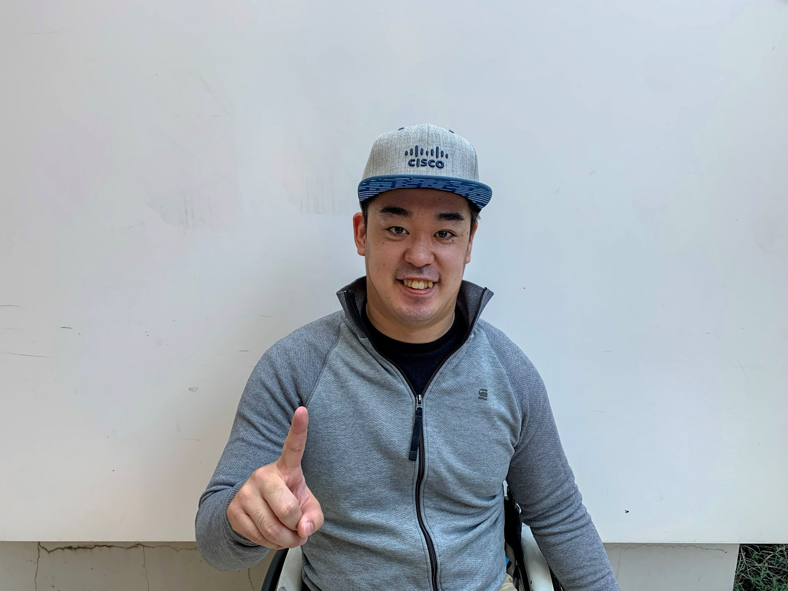 Hideaki wears a Cisco hat and holds up his finger as #1.