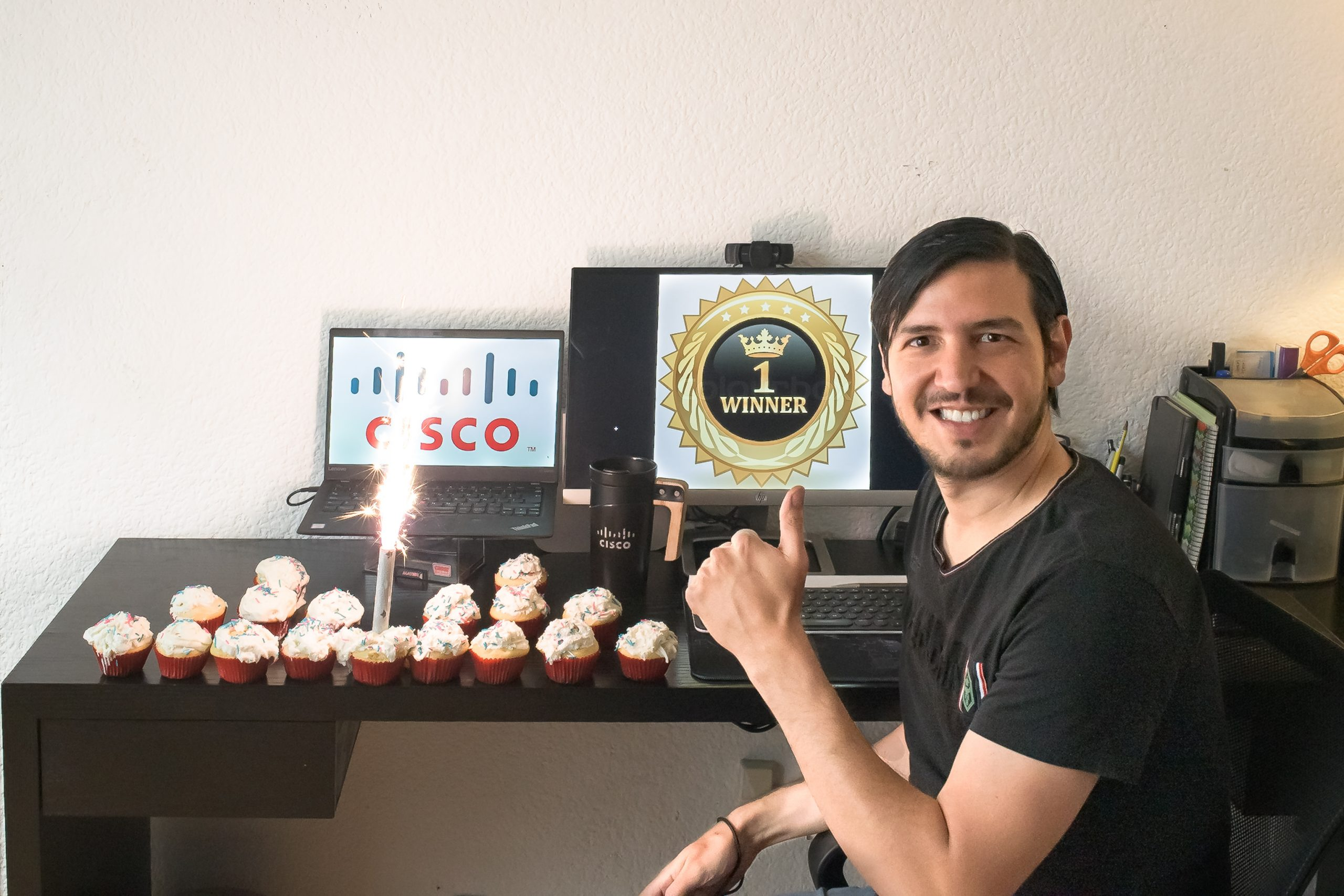 Javier sits at his desk with cupcakes in the shape of a Cisco logo and holds up his finger as #1.
