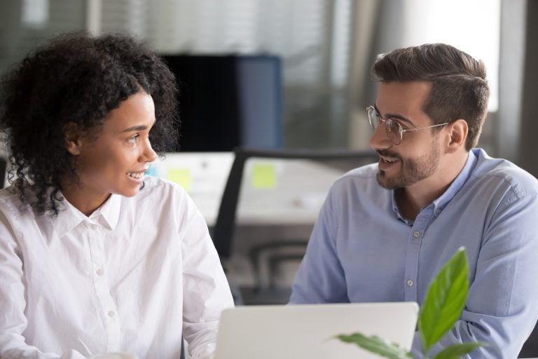 Multiracial diverse workers african woman and caucasian man communicating sitting opposite laptop at desk in office. Black manager female talking with coworker man discussing new project sharing ideas