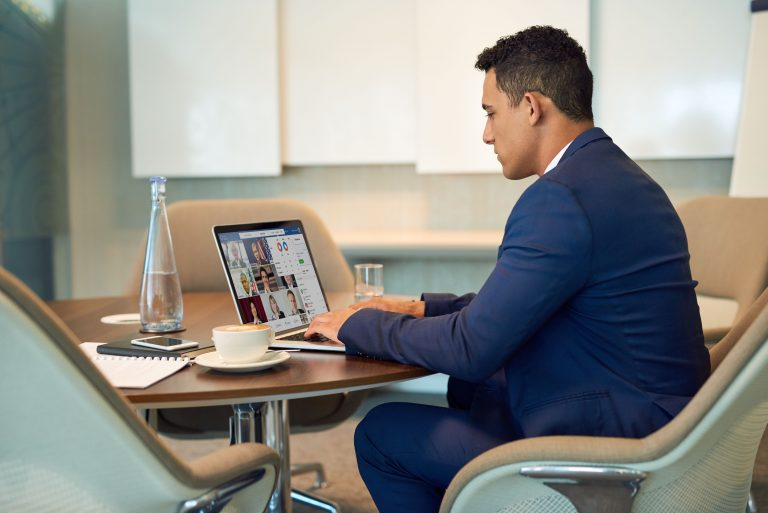 man sitting at desk on computer working