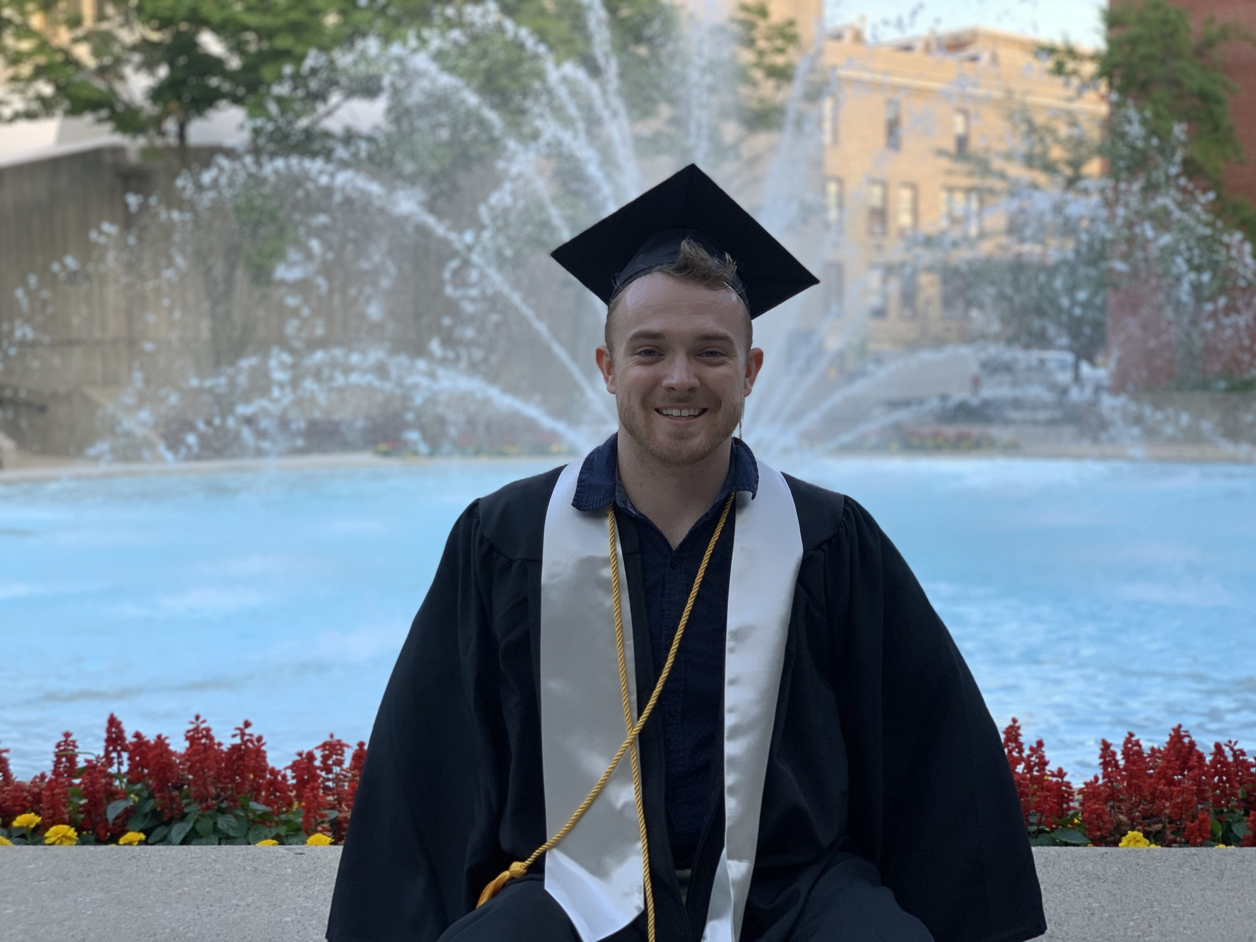 Nathan in cap and gown sitting in front of fountain.