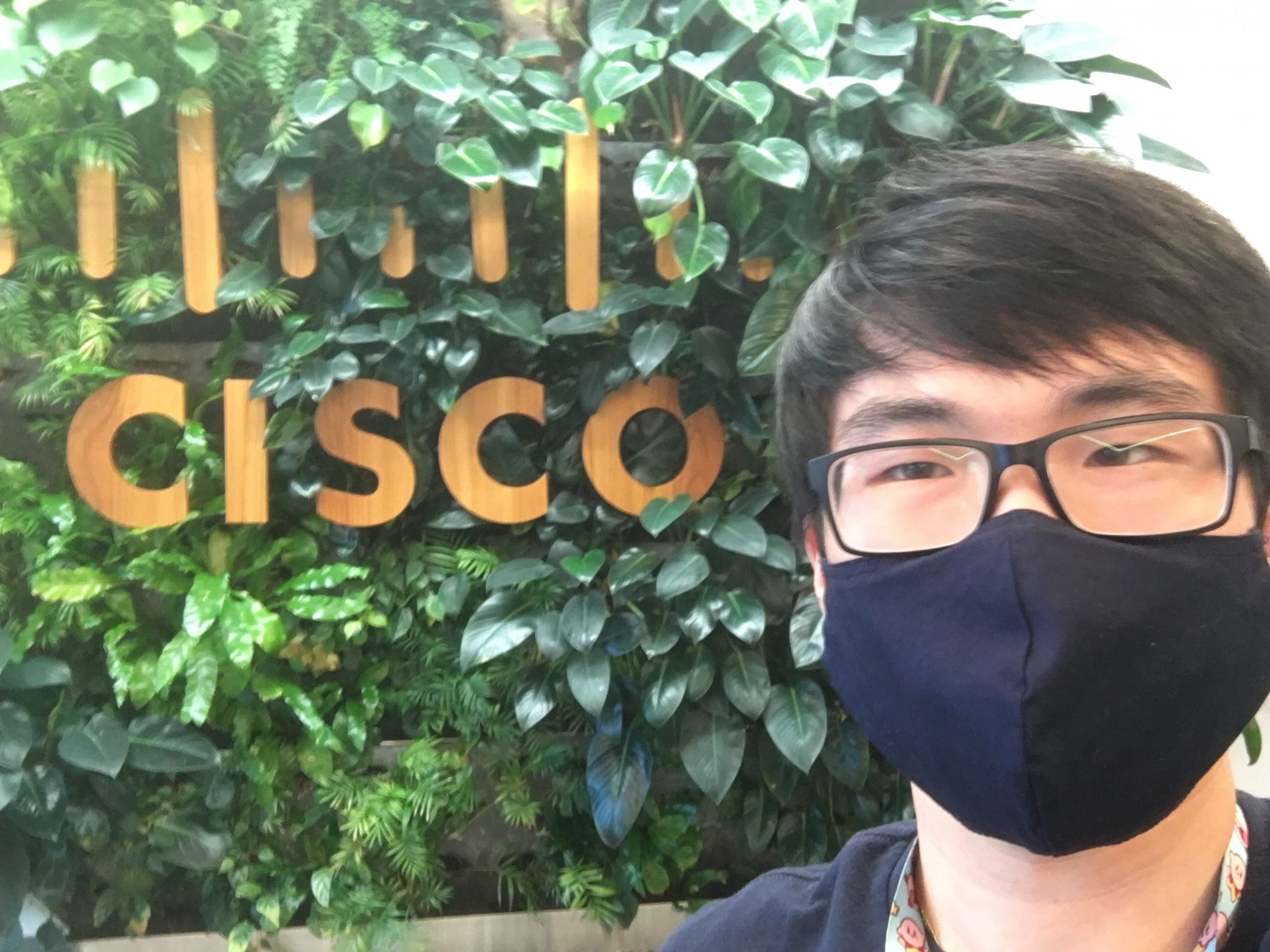 Bryce with mask in front of Cisco sign.