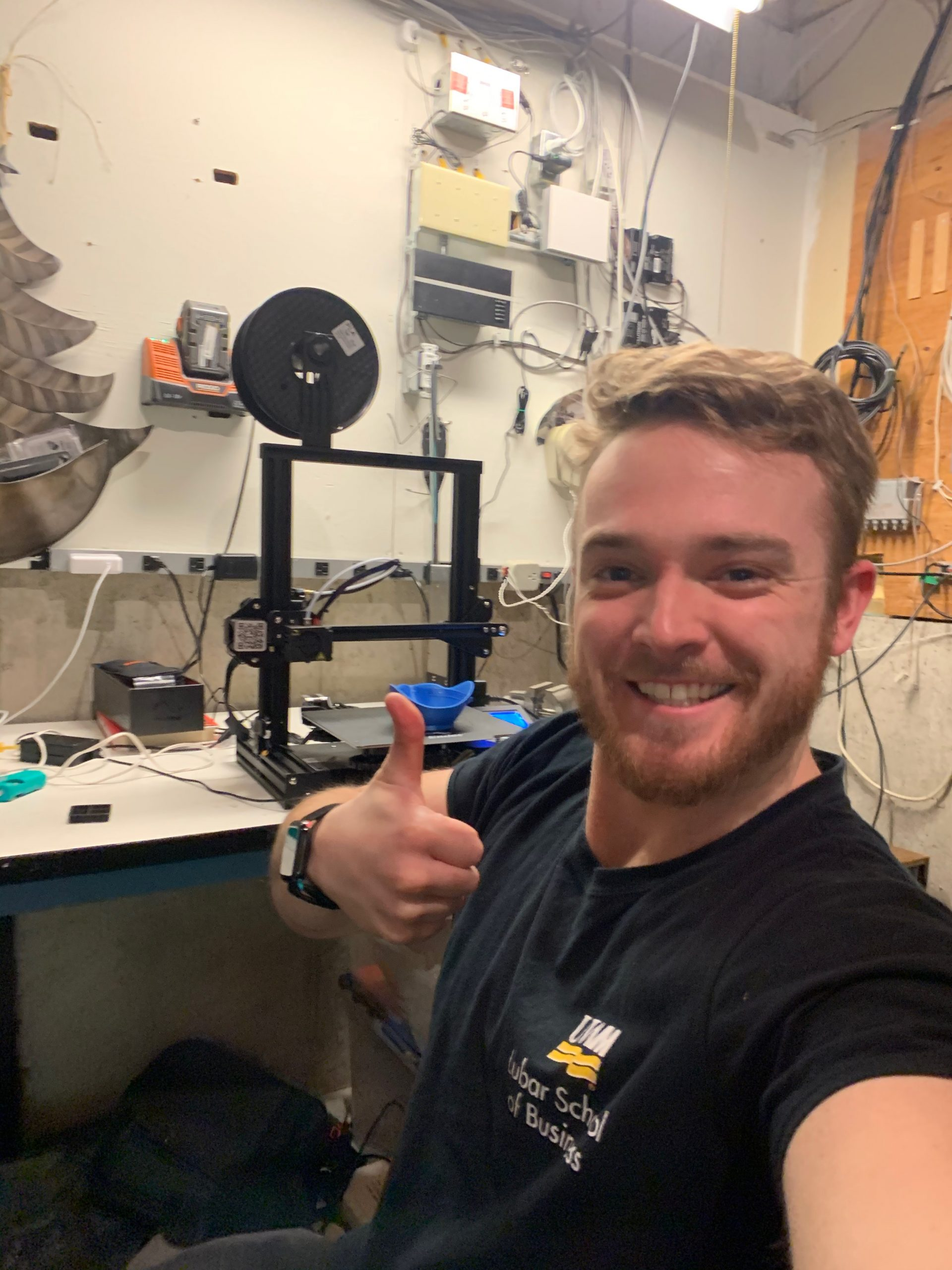 Nathan giving thumbs up in front of 3D printer.